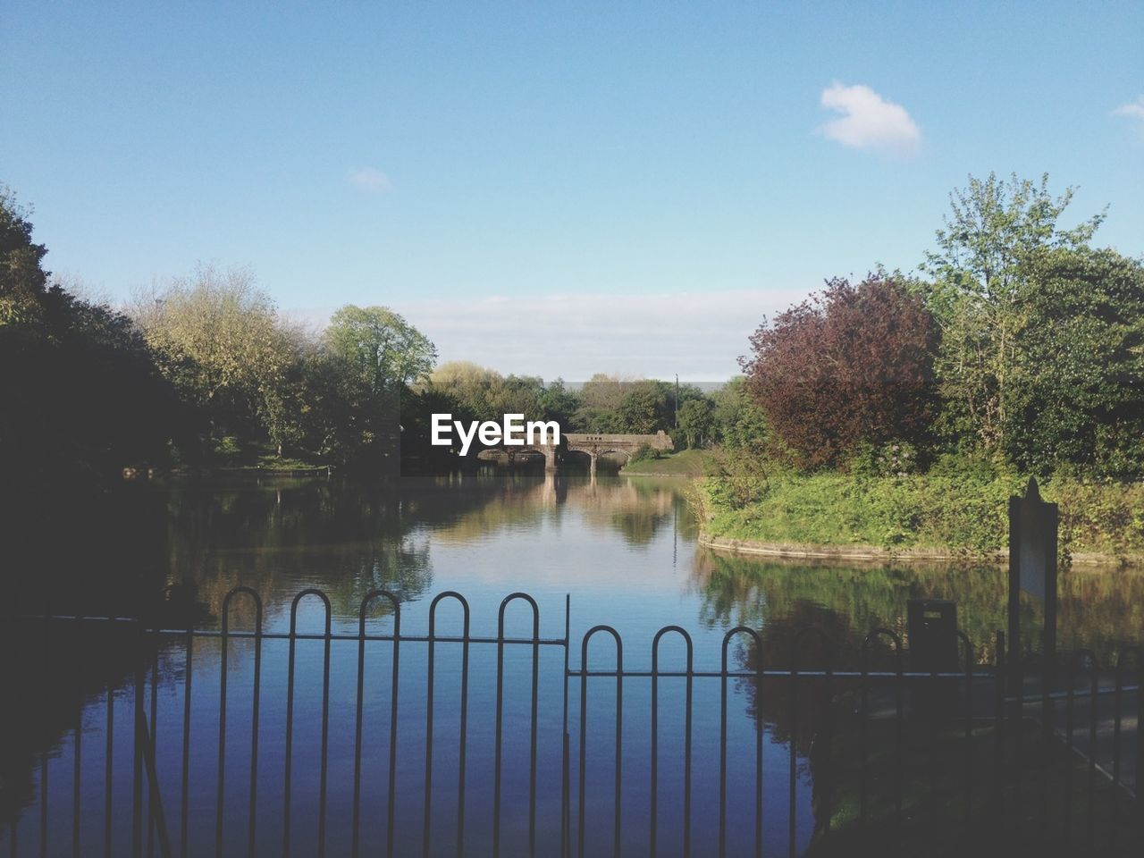 Railing by river and trees against sky