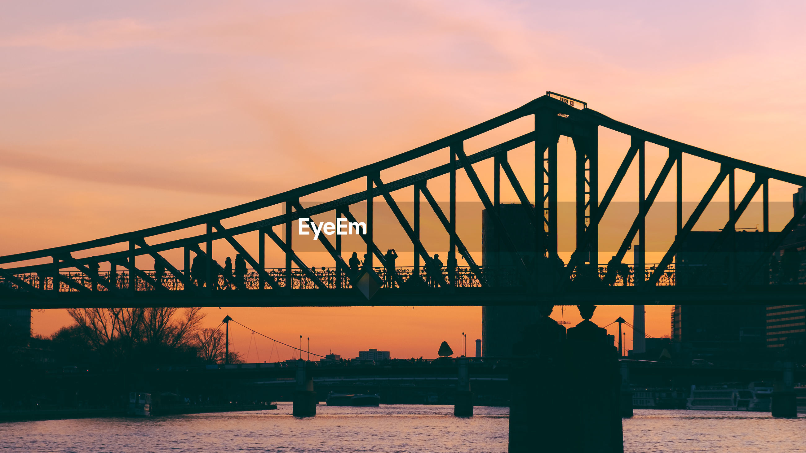 Silhouette of metallic bridge over river against sky during sunset