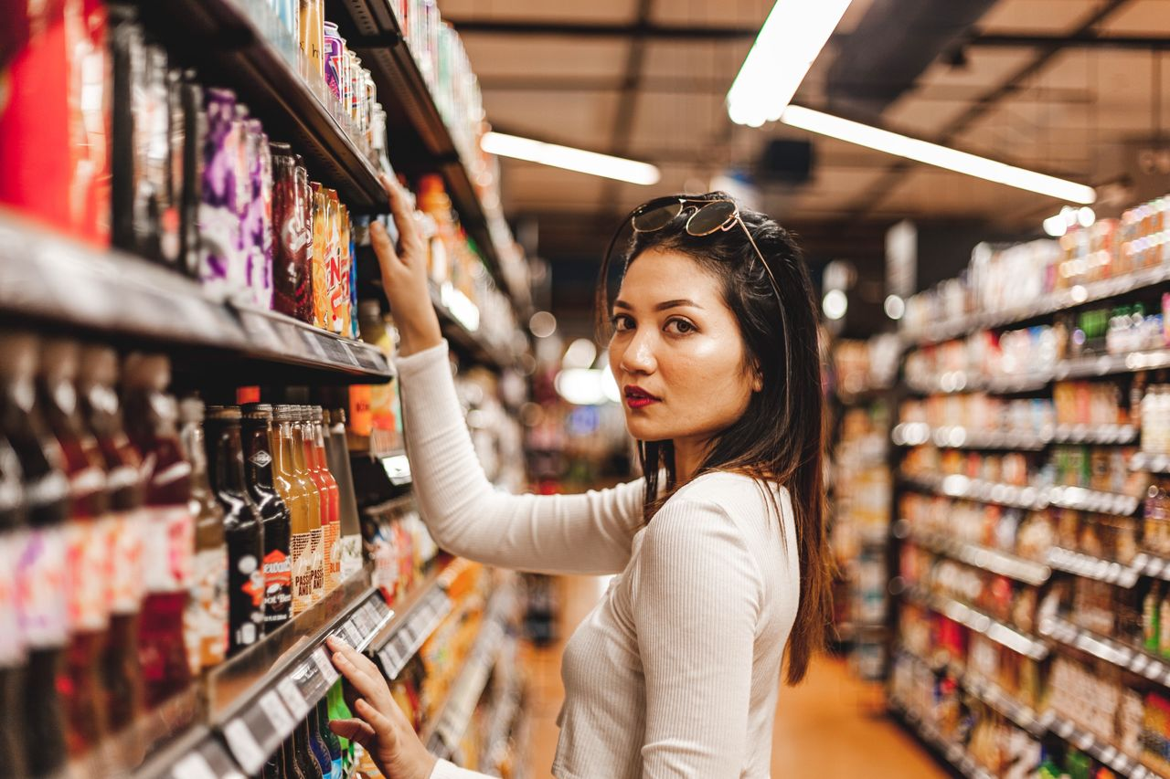 one person, retail, store, adult, choice, women, shopping, supermarket, young adult, shelf, young women, side view, consumerism, market, lifestyles, variation, food and drink, standing, indoors, groceries, hair, hairstyle, buying, beautiful woman