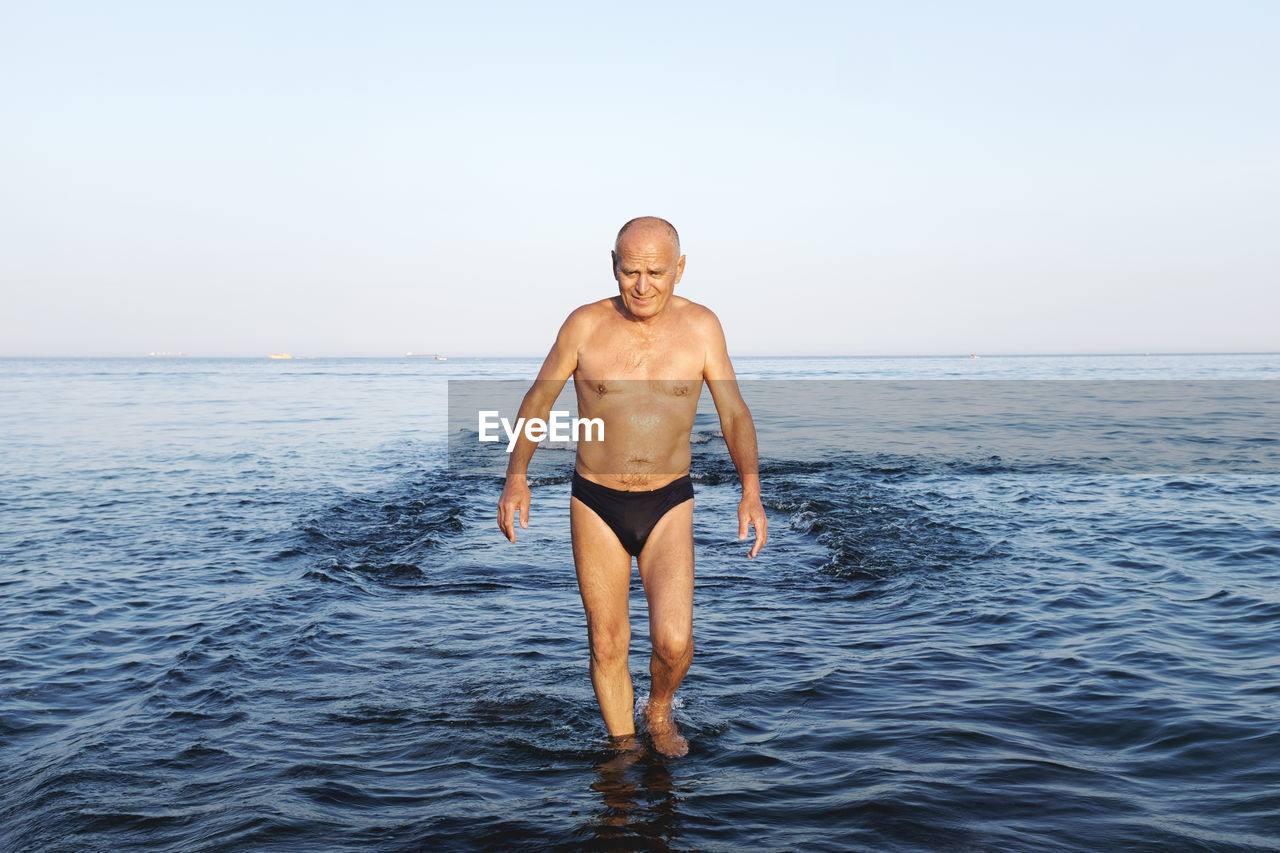 Shirtless Man Wading In Sea Against Sky