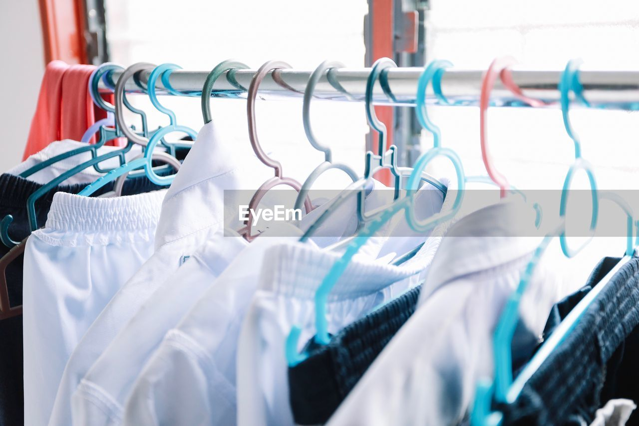 coathanger, rack, hanging, clothing, no people, in a row, textile, clothes rack, metal, close-up, choice, large group of objects, day, indoors, laundry, selective focus, group of objects, variation, focus on foreground, absence, garment, clean