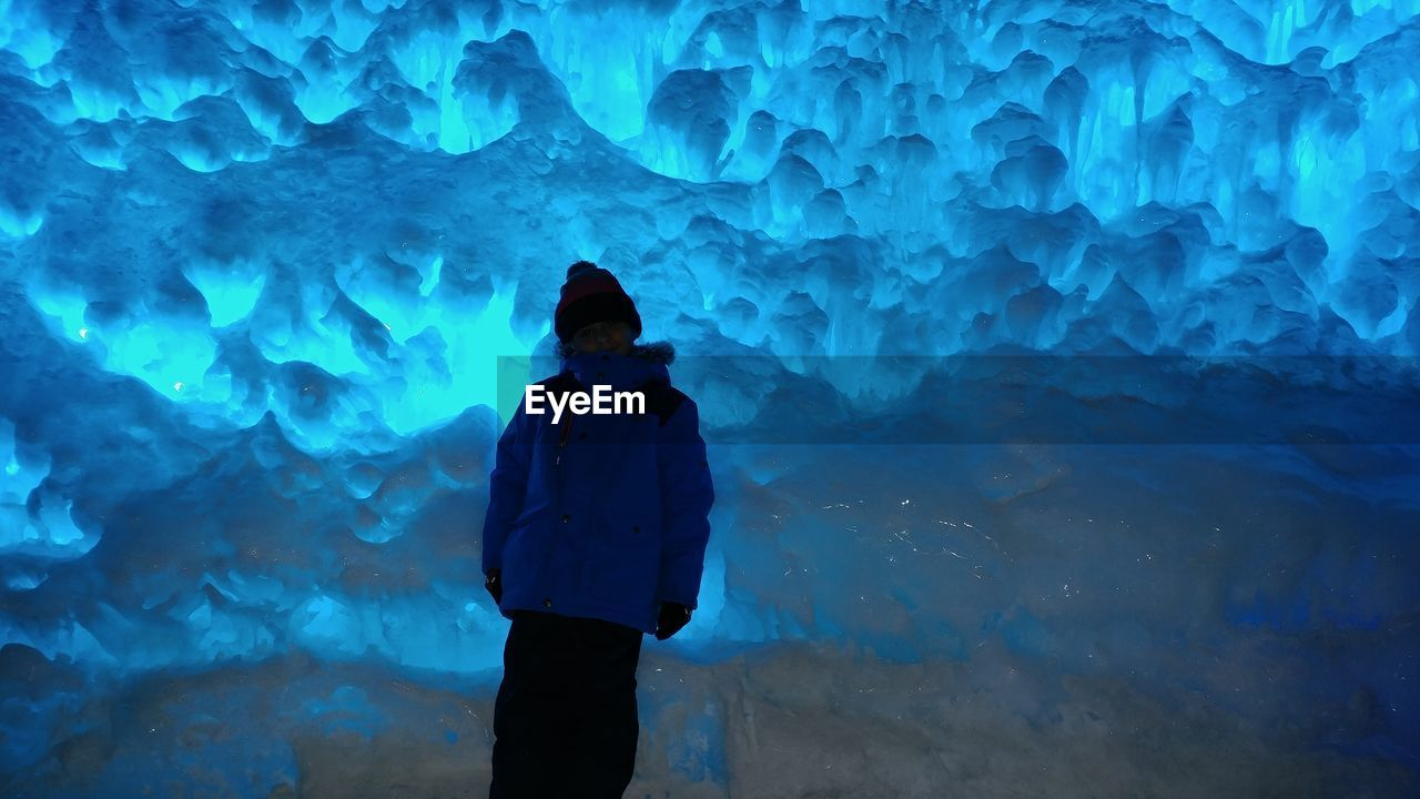 Boy wearing warm clothing standing in ice cave