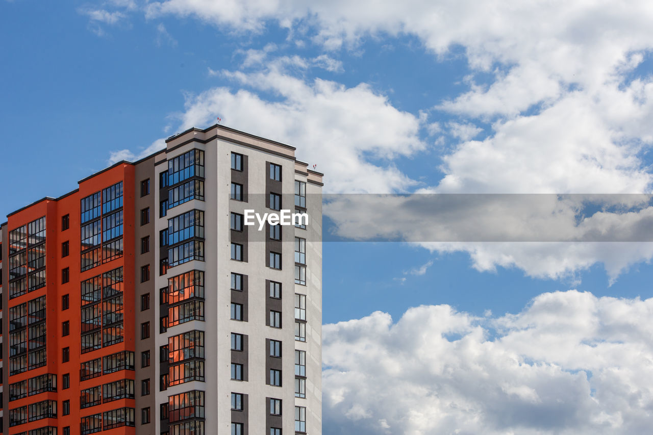 New high rise apartament building with  balcony and windows on blue sky with white clouds background