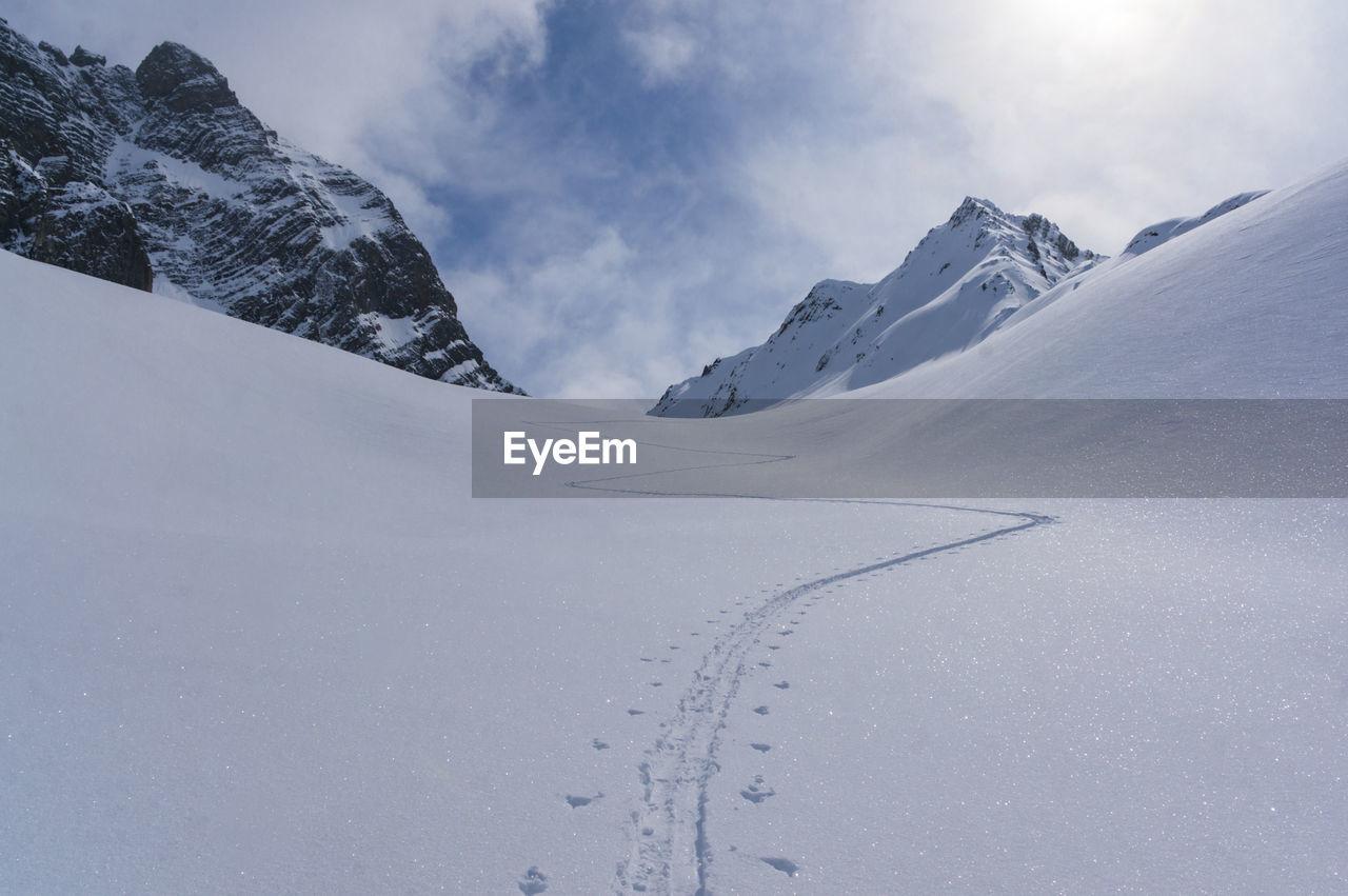 Ski Track On Snowcapped Mountain Against Sky
