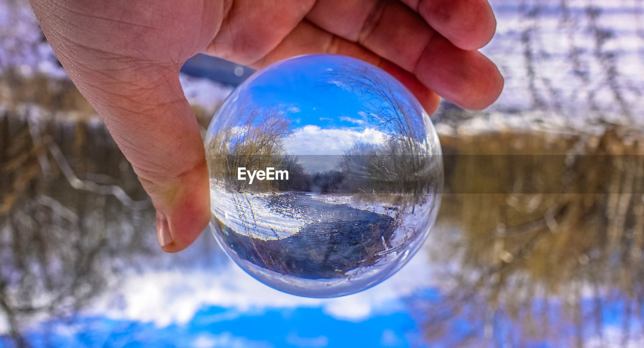 sphere, reflection, glass - material, crystal ball, holding, crystal, human hand, human finger, human body part, close-up, real people, tree, upside down, planet earth, planet - space, focus on foreground, one person, day, outdoors, men, sky, nature, fragility, people