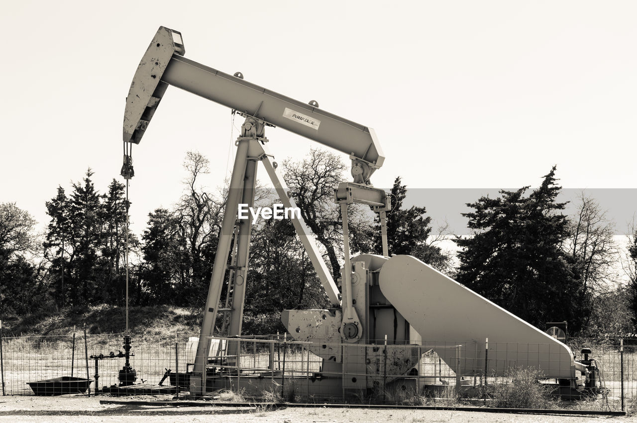 oil pump, tree, oil field, oil industry, clear sky, no people, outdoors, oil well, industrial equipment, day, sky, drilling rig