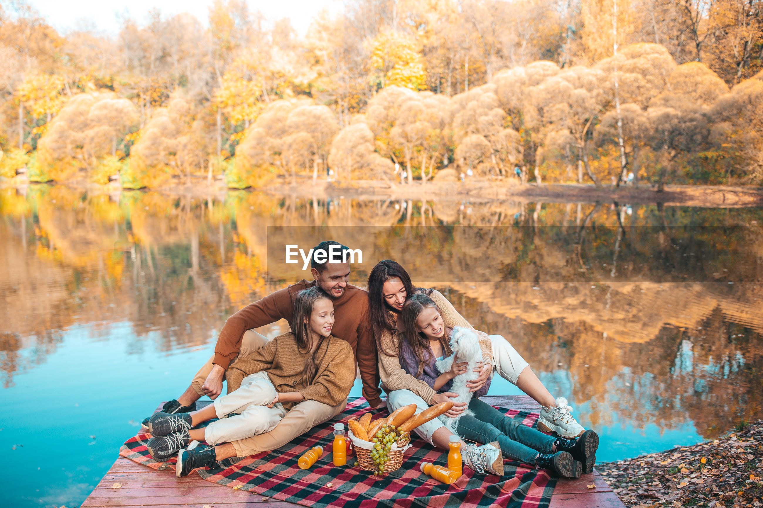 Cheerful family sitting on pier by lake at forest