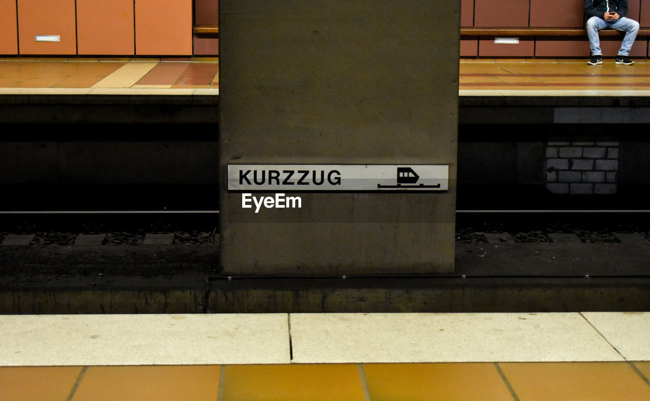 text, architecture, communication, western script, railroad station platform, railroad station, rail transportation, transportation, built structure, public transportation, sign, mode of transportation, no people, indoors, wall - building feature, number, subway, track, station