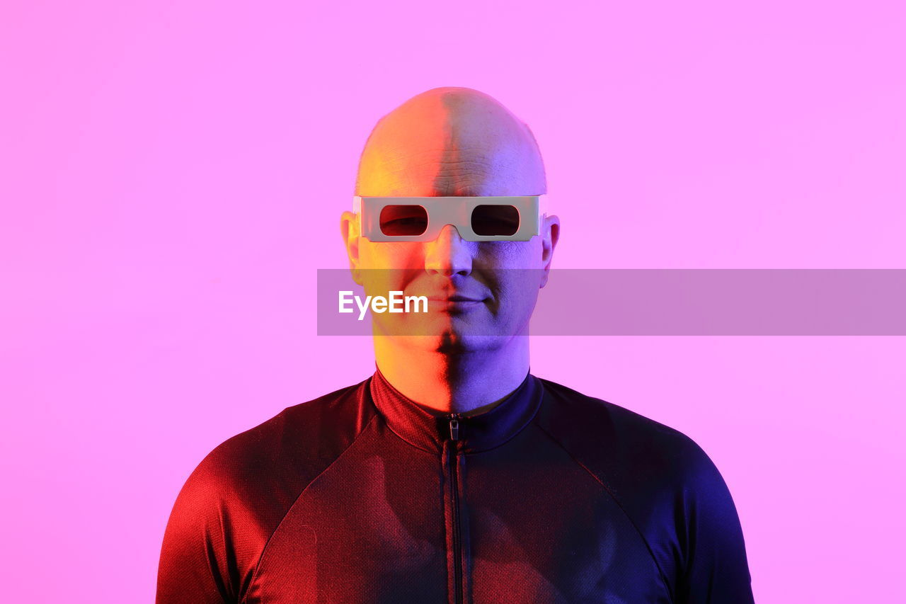 Man Wearing 3-D Glasses Against Pink Background