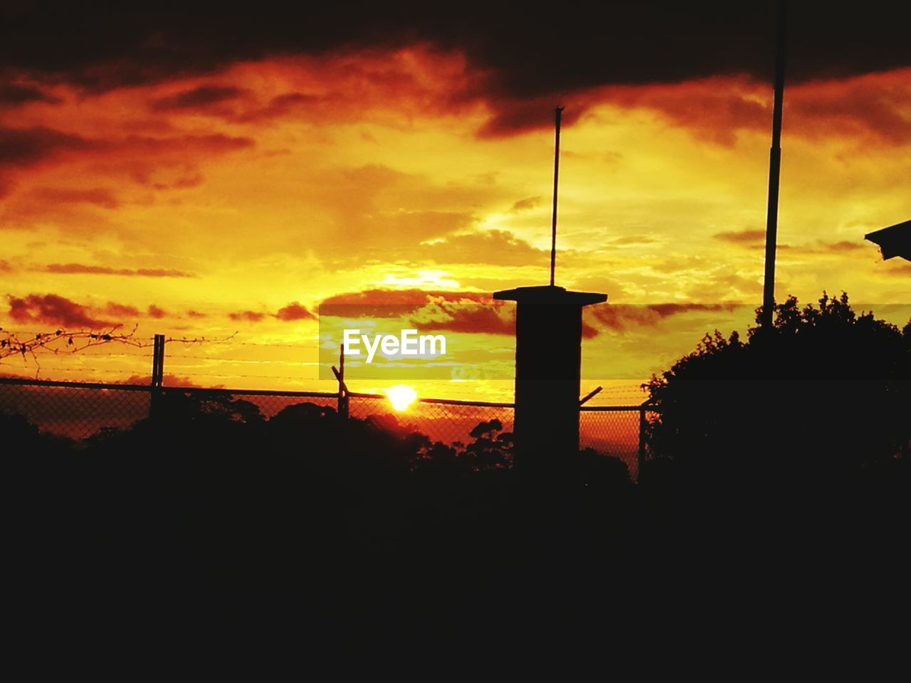 sunset, silhouette, orange color, sky, cloud - sky, dramatic sky, nature, beauty in nature, no people, scenics, outdoors, built structure, architecture, tree, city