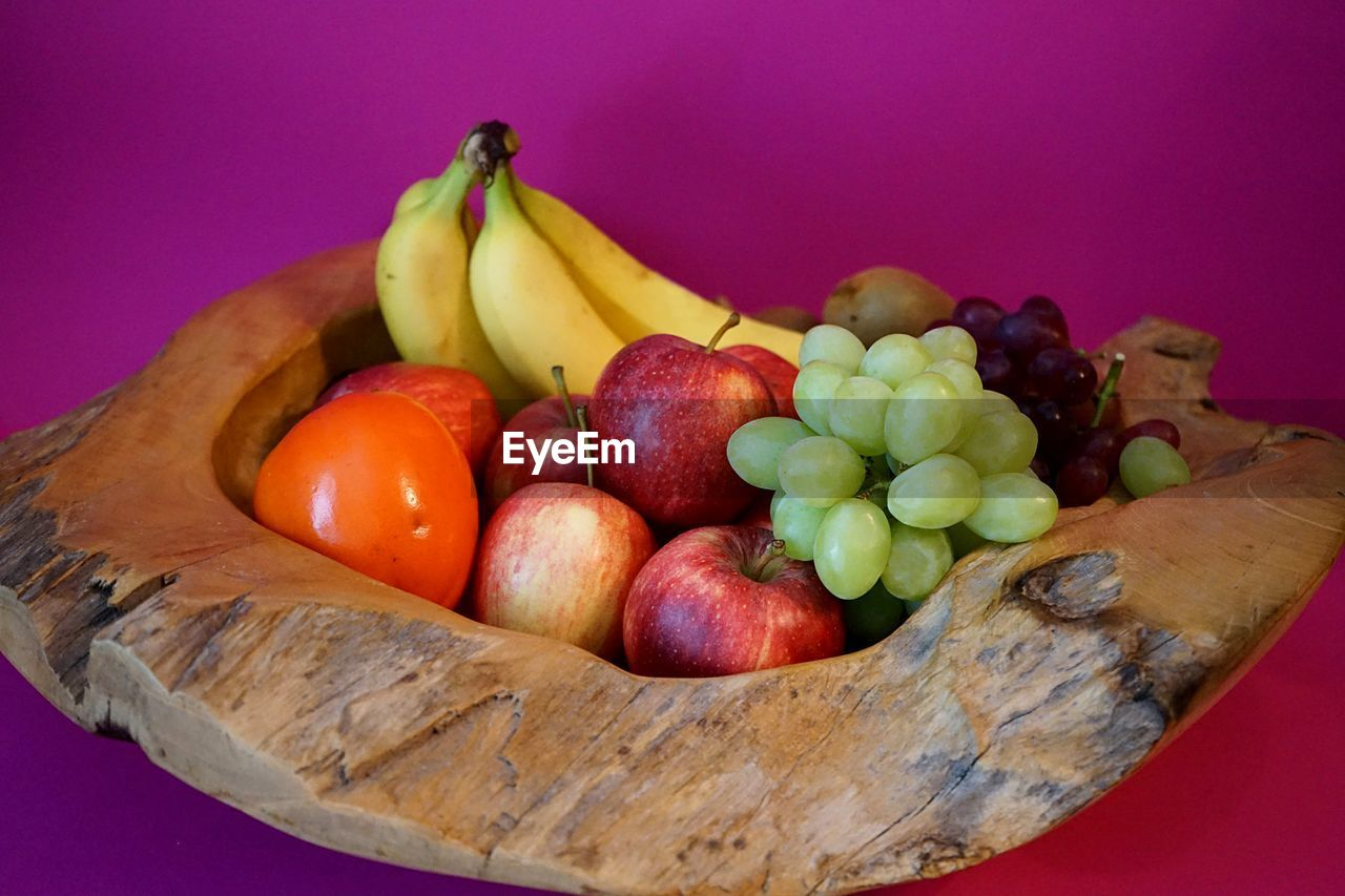 food, food and drink, healthy eating, fruit, wellbeing, freshness, still life, banana, indoors, close-up, no people, table, studio shot, wood - material, variation, choice, grape, red, colored background, high angle view