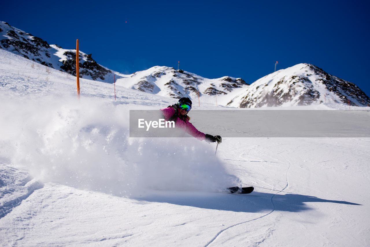snow, winter, cold temperature, mountain, sport, nature, skiing, adventure, white color, ski holiday, snowcapped mountain, weather, motion, winter sport, leisure activity, ski pole, day, beauty in nature, vacations, lifestyles, scenics, real people, ski goggles, outdoors, extreme sports, fun, speed, activity, one person, sunlight, mountain range, snowboarding, full length, skill, clear sky, men, sky, people