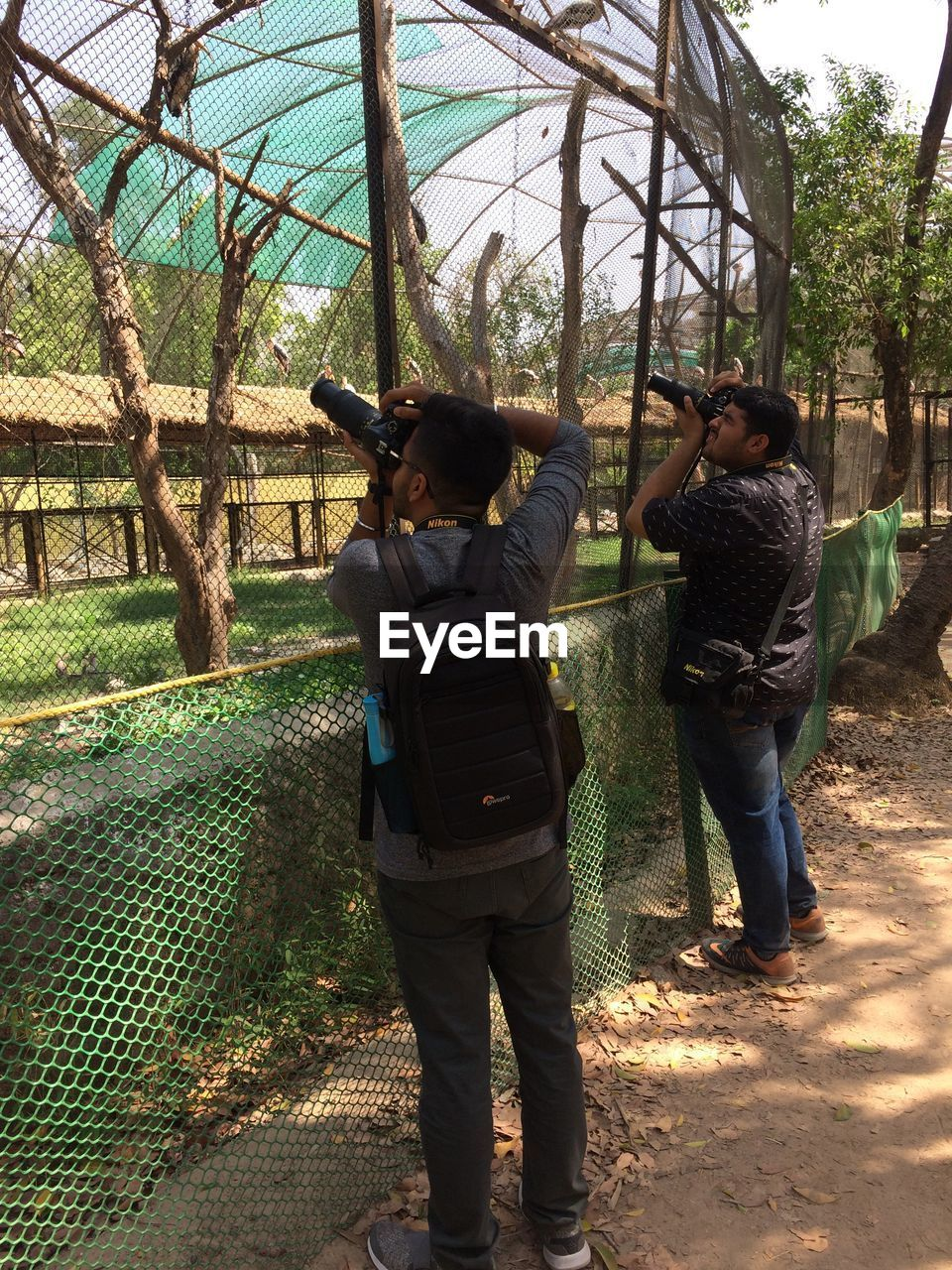 real people, full length, casual clothing, men, two people, standing, rear view, people, lifestyles, nature, fence, togetherness, leisure activity, adult, women, bonding, barrier, boundary, day, plant, outdoors, positive emotion, couple - relationship, warm clothing, sister