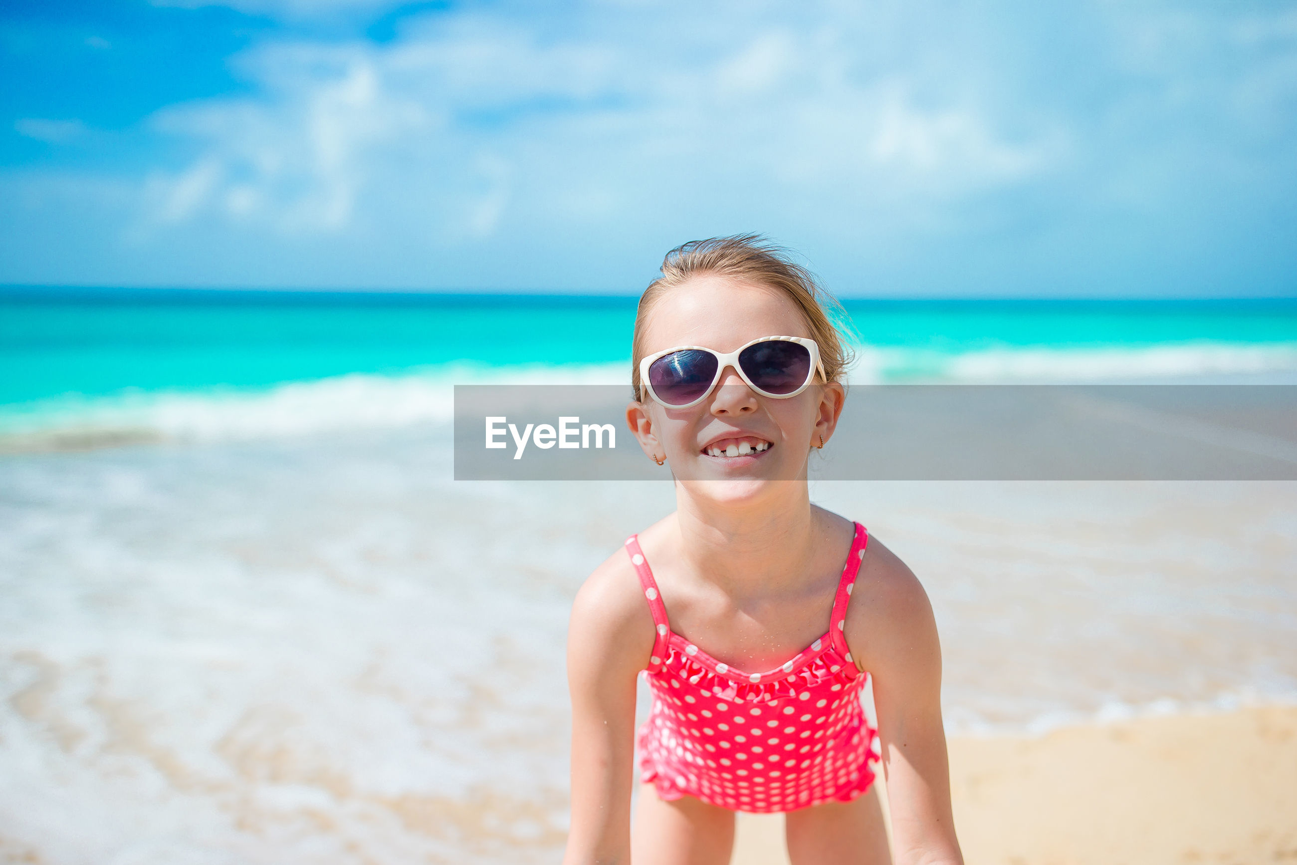 PORTRAIT OF BOY WEARING SUNGLASSES AT BEACH