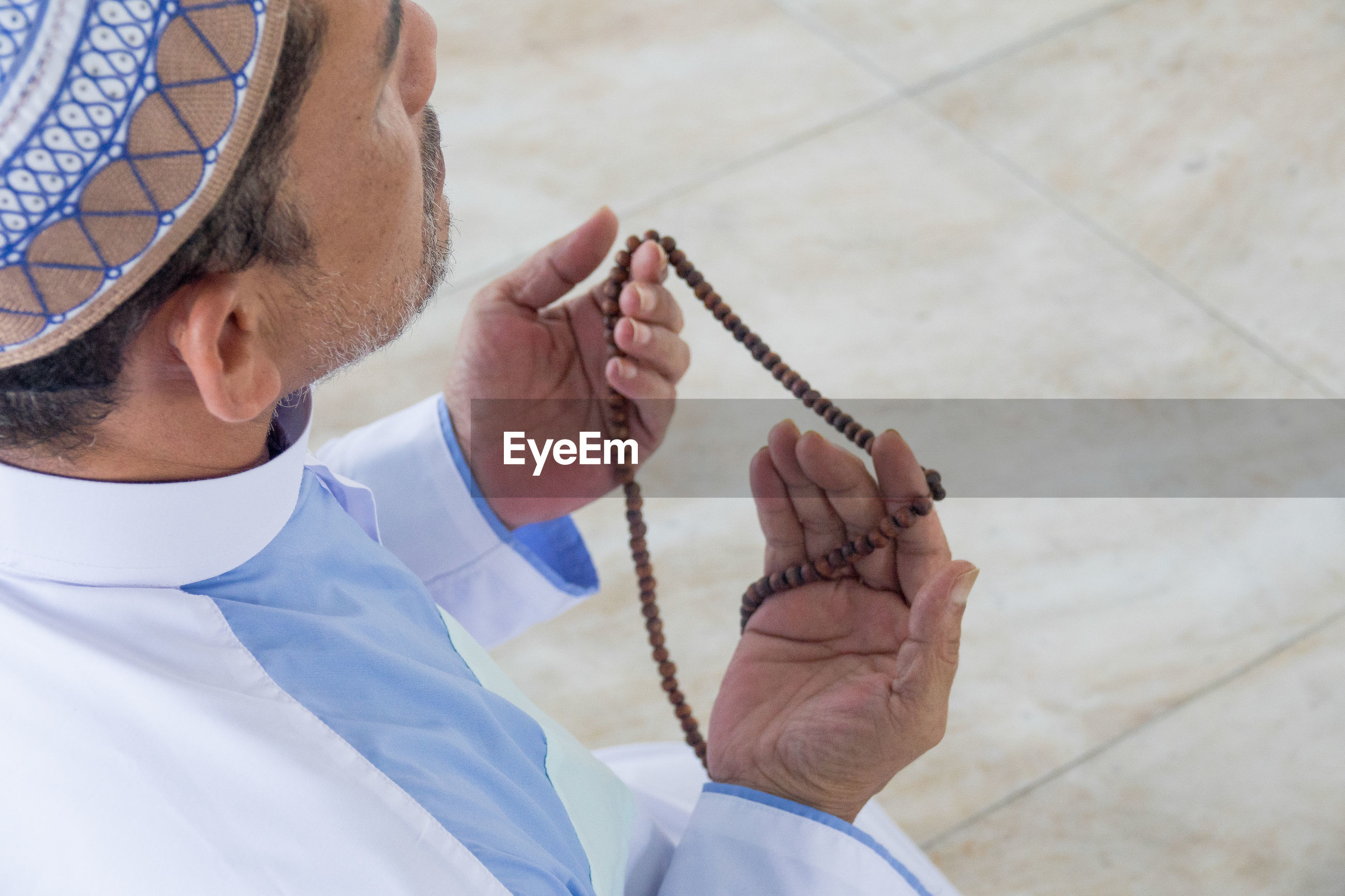 Man holding prayer beads while praying at mosque