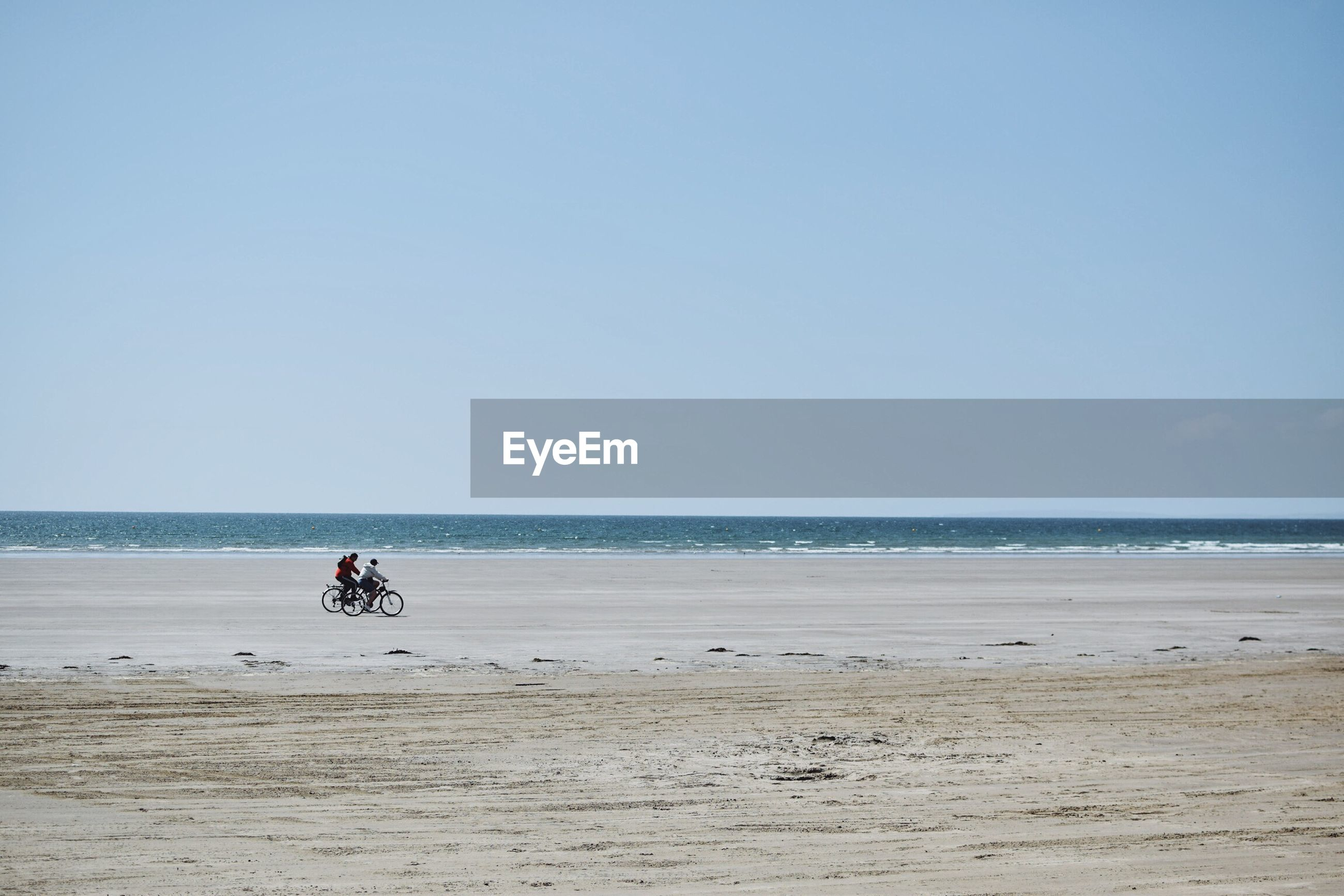 Side view of men riding bicycles at beach