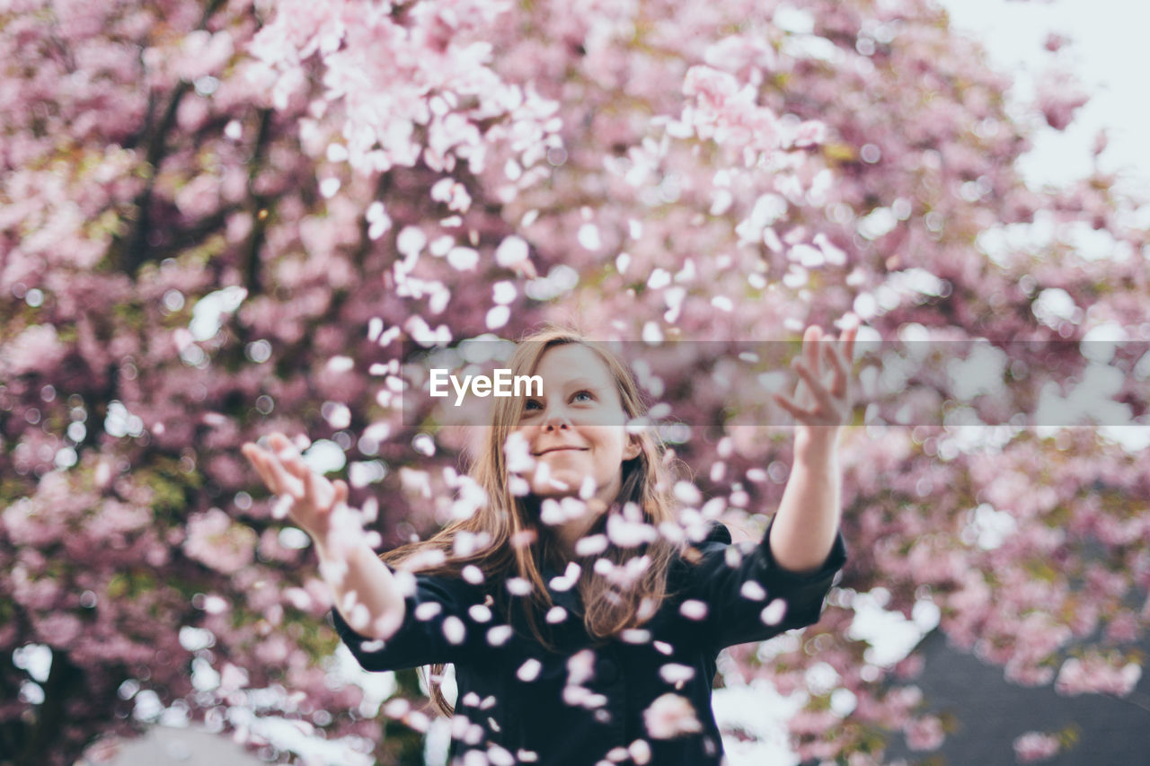 Portrait Of Smiling Girl Throwing Flower Petals