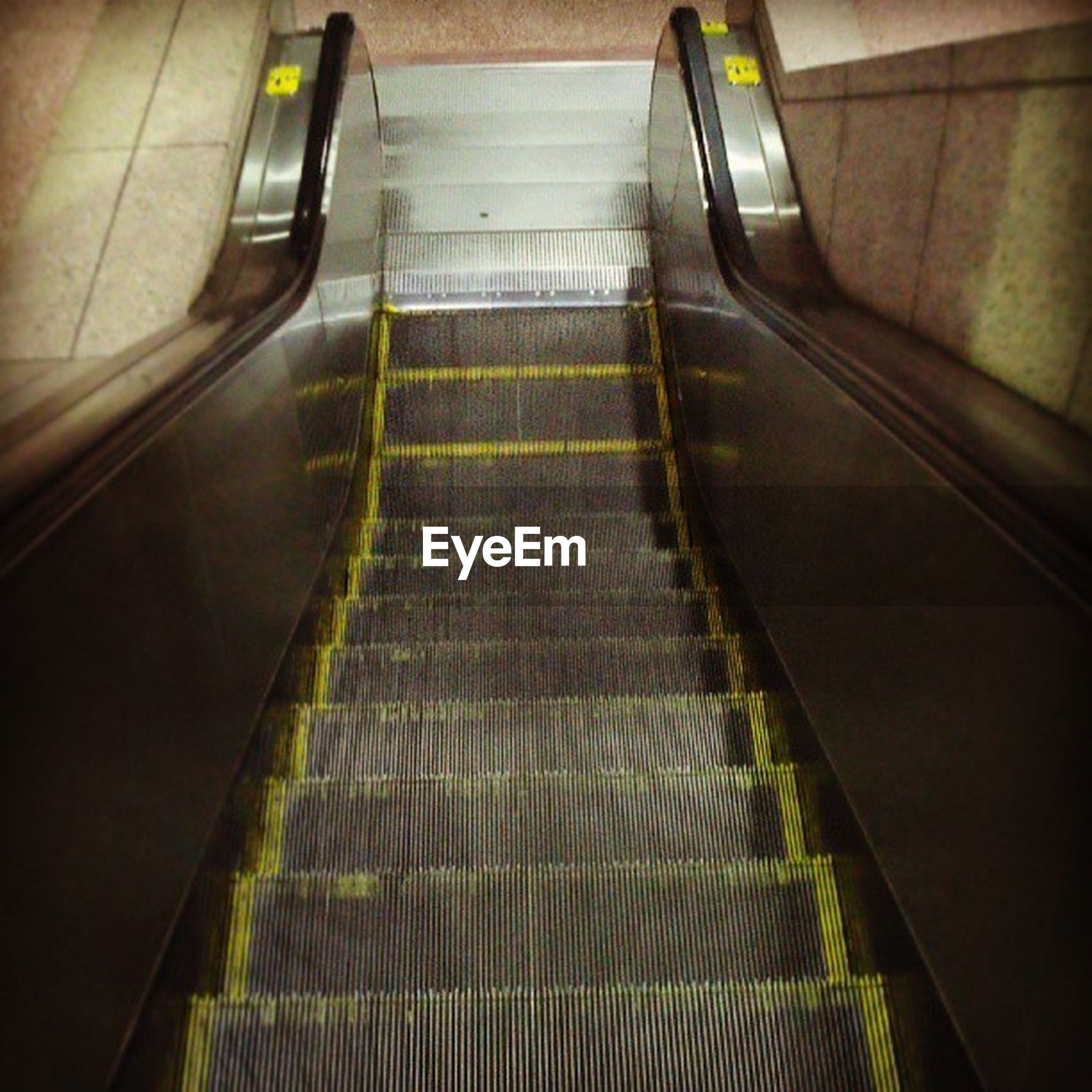 indoors, transportation, high angle view, the way forward, steps, escalator, railing, steps and staircases, staircase, empty, absence, diminishing perspective, mode of transport, no people, modern, on the move, convenience, sunlight, illuminated, vanishing point