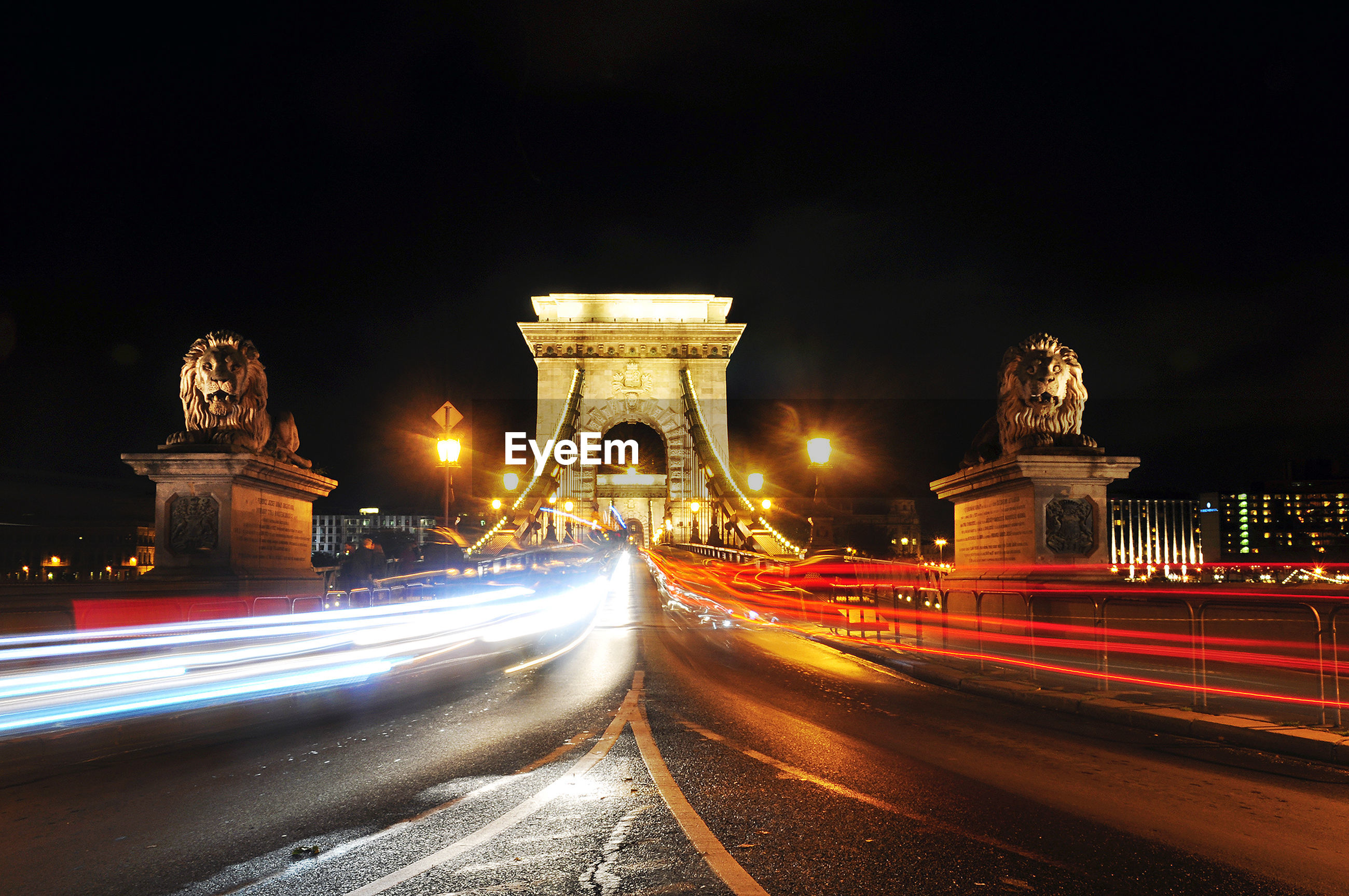 Light trails on chain bridge against clear sky at night