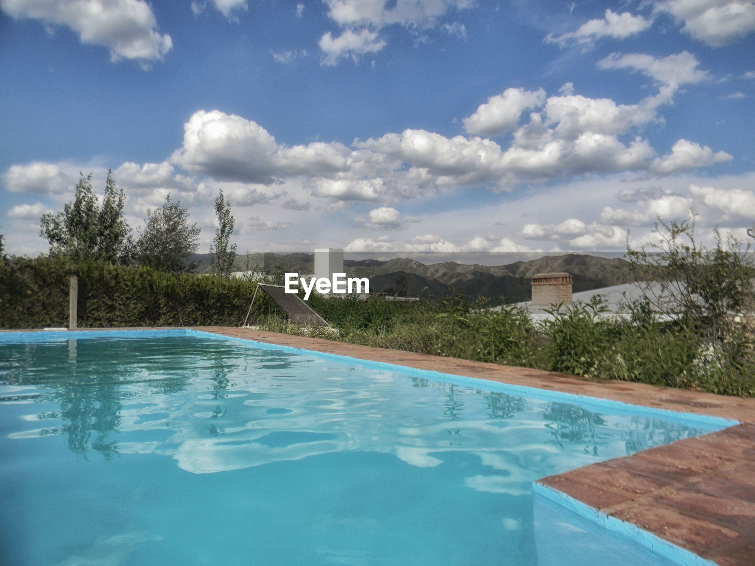 VIEW OF SWIMMING POOL BY TREES AGAINST SKY