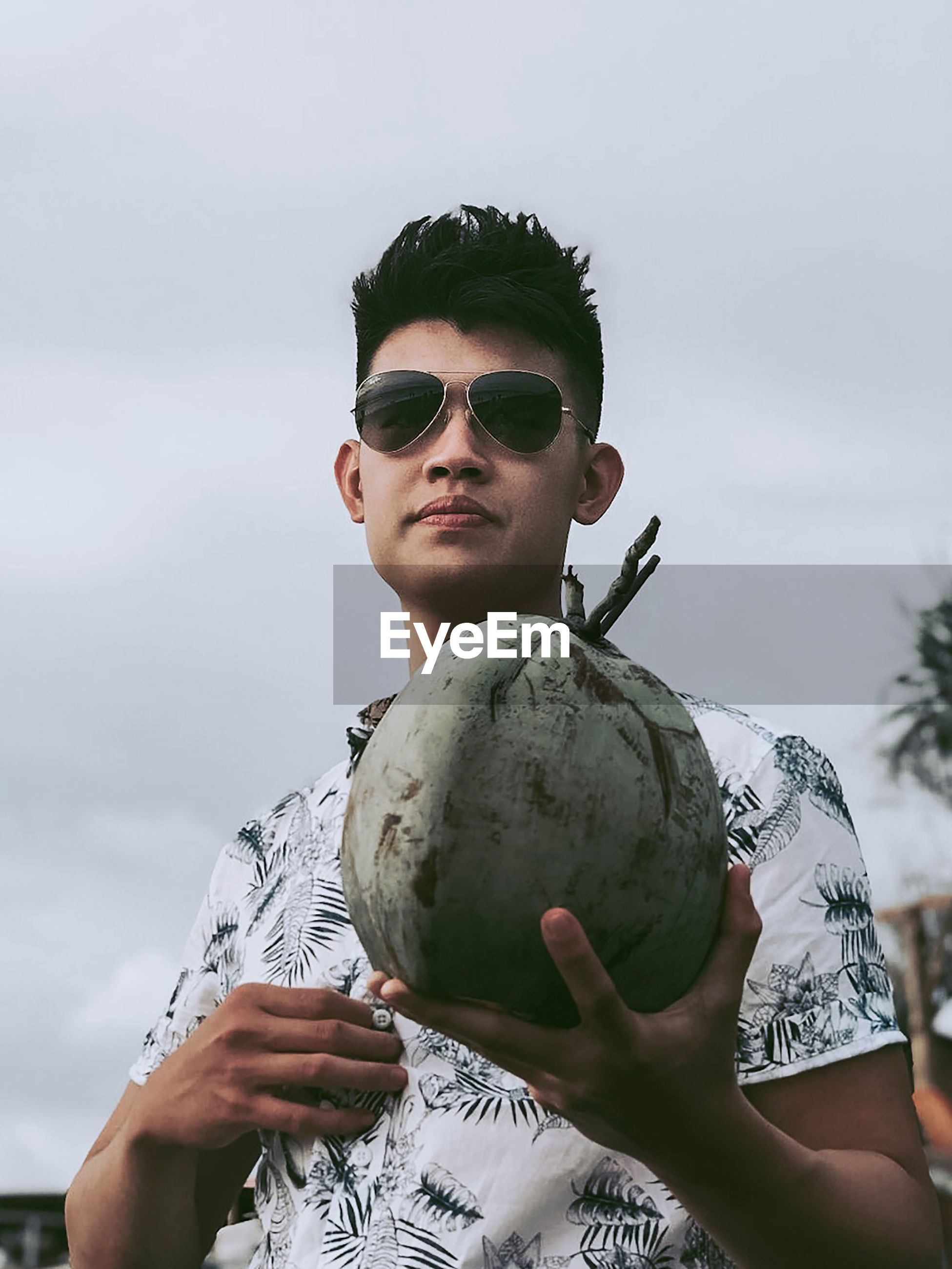 Portrait of young man holding coconut against sky