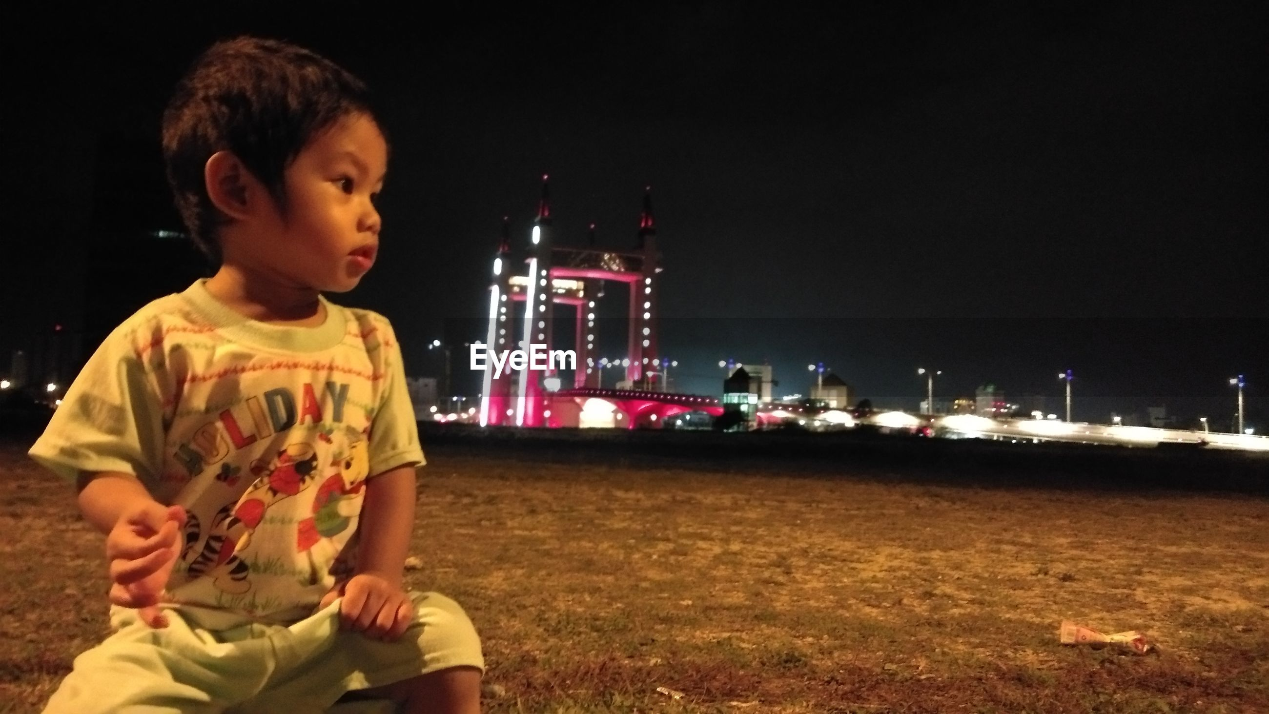 BOY LOOKING AWAY WHILE SITTING ON LAND
