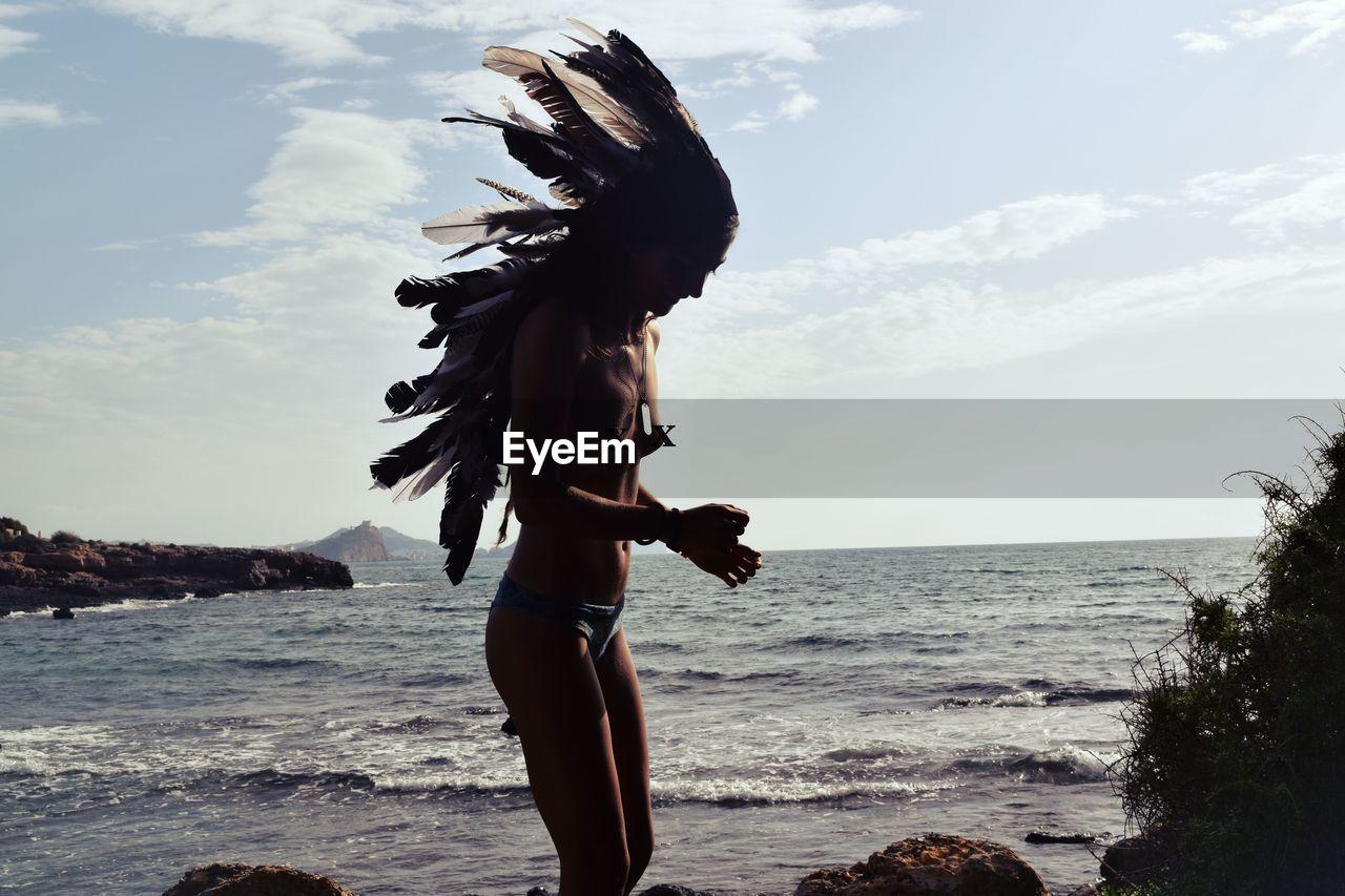 Woman wearing headdress standing at beach against sky