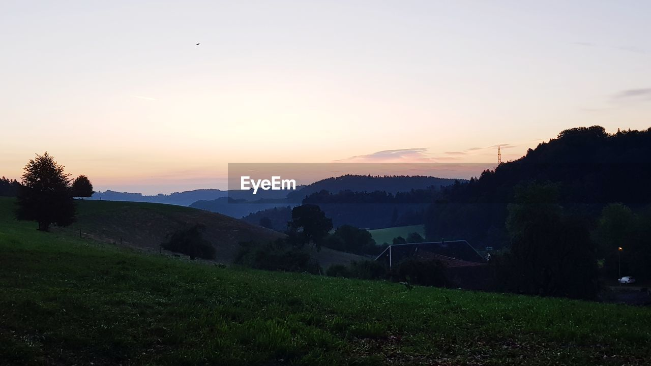 sky, sunset, scenics - nature, plant, beauty in nature, tranquil scene, tranquility, tree, nature, environment, orange color, landscape, no people, non-urban scene, idyllic, field, mountain, grass, outdoors, land