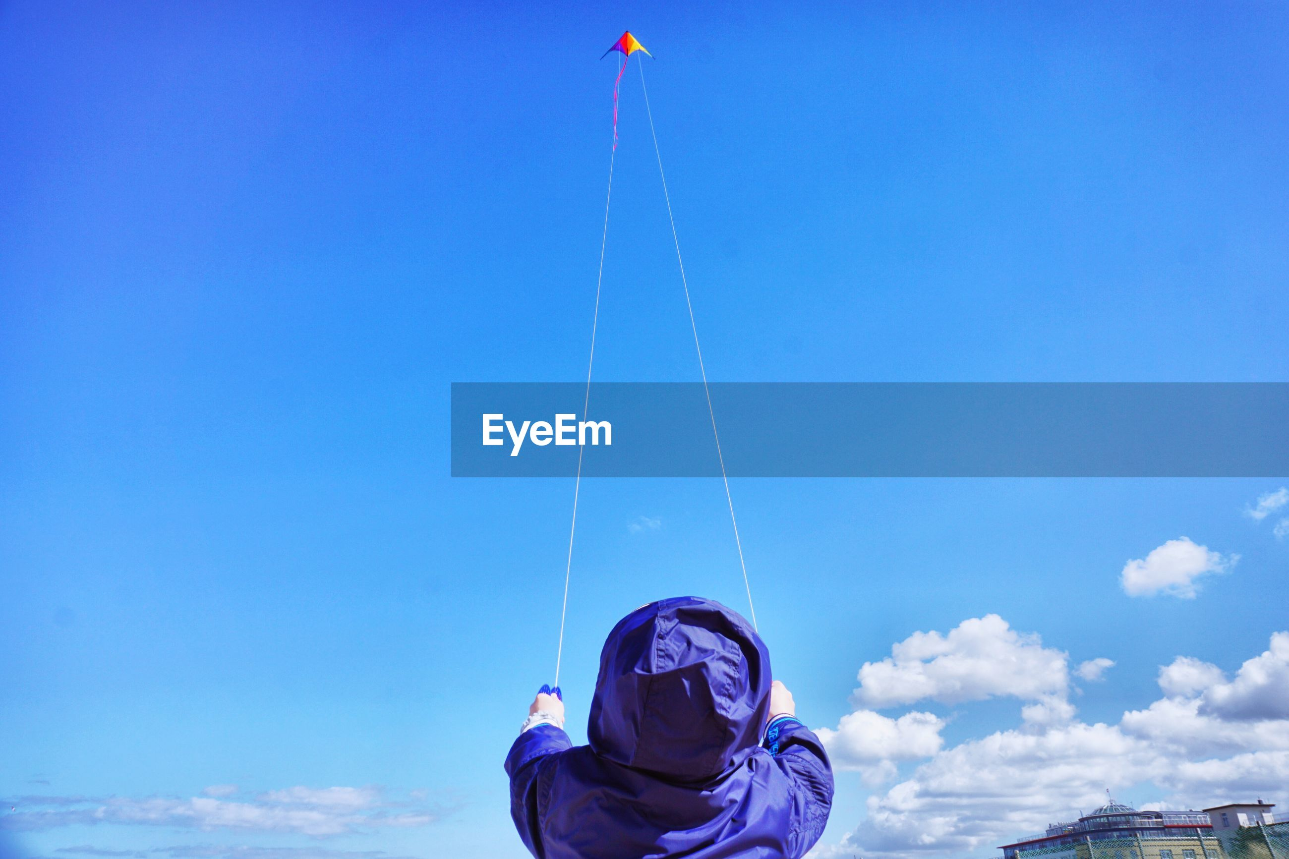 Rear view of boy flying kite against blue sky