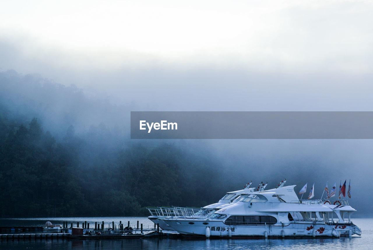 Yachts Moored At Harbor In Lake