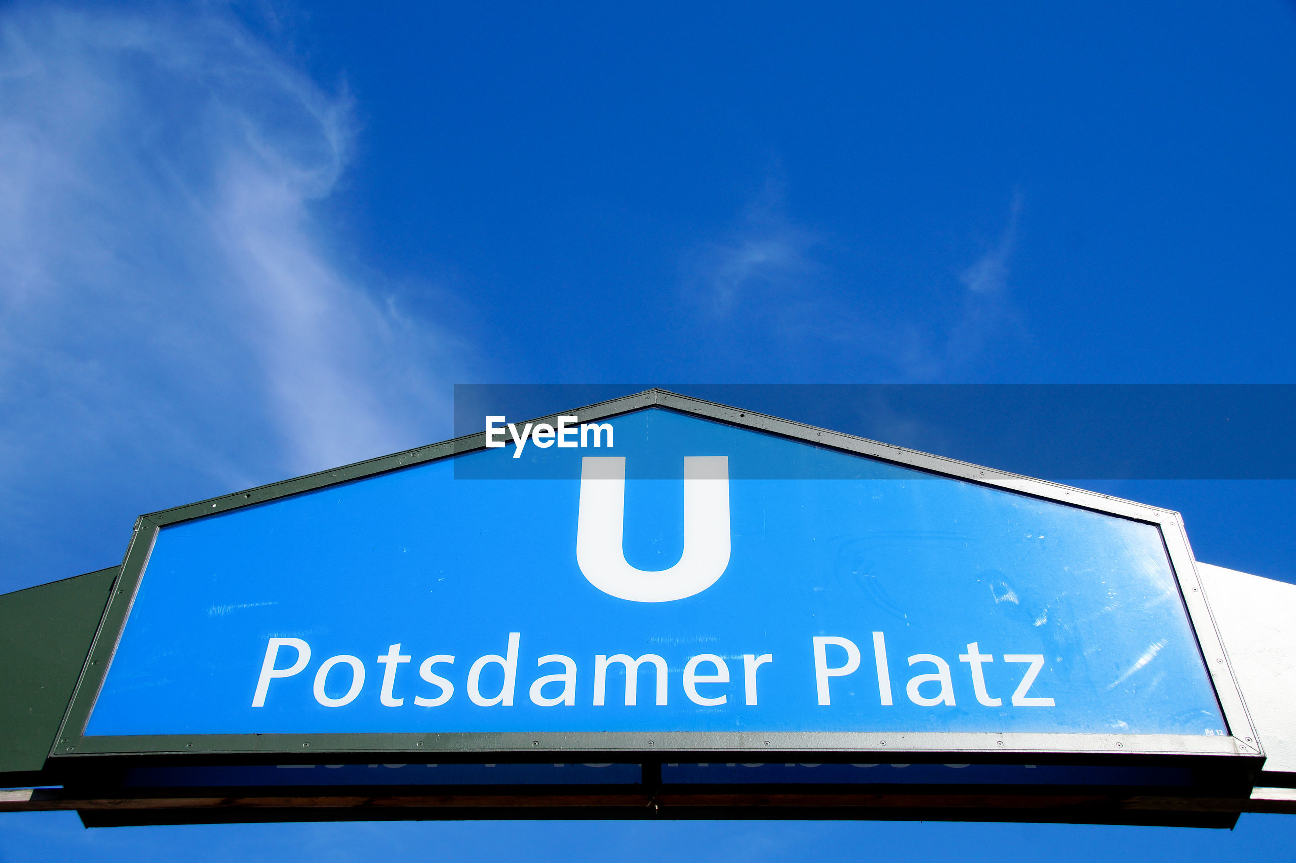 Low angle view of potsdamer platz sign against blue sky