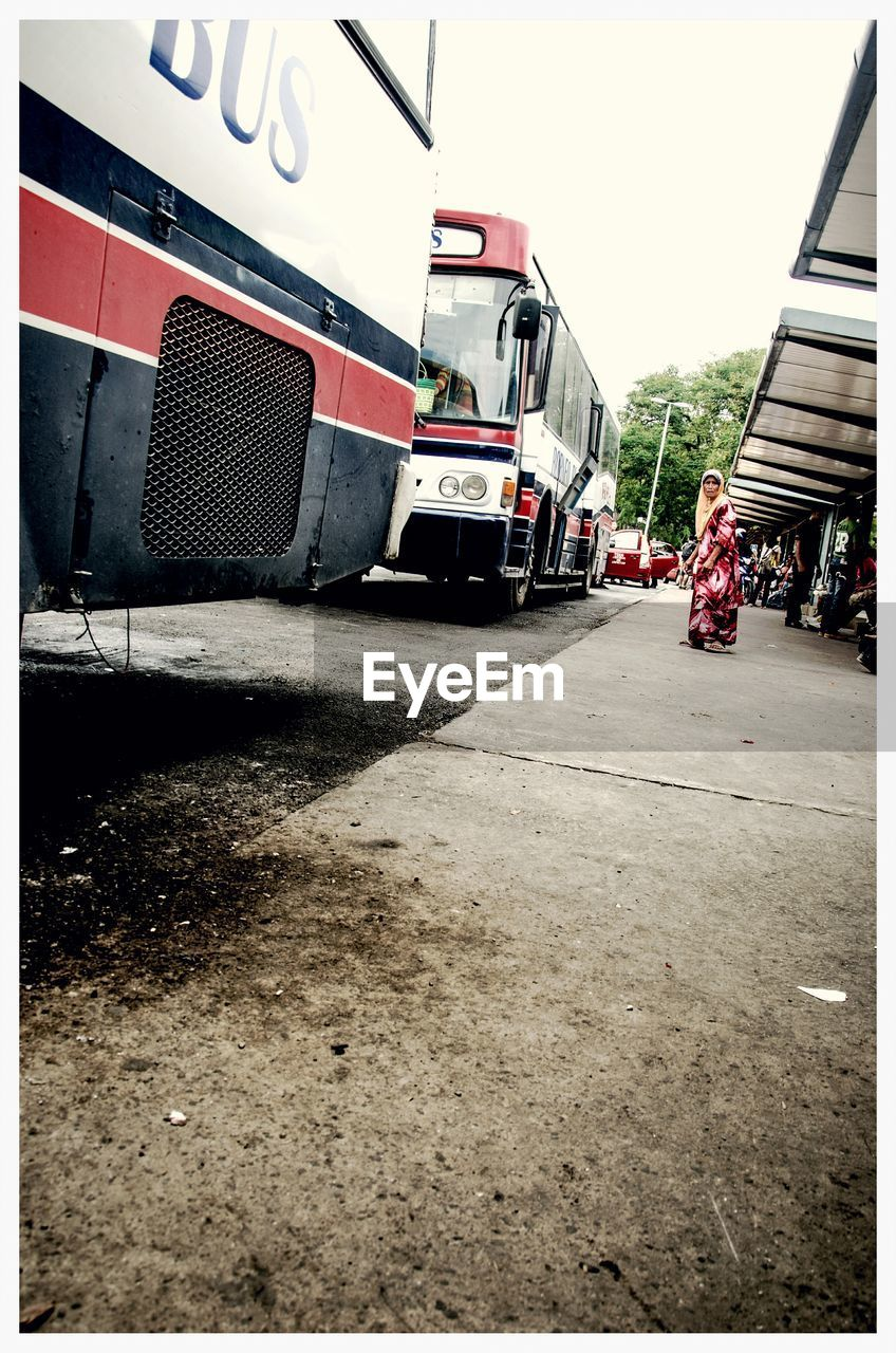 Low Angle View Of Woman At Bus Stop In City