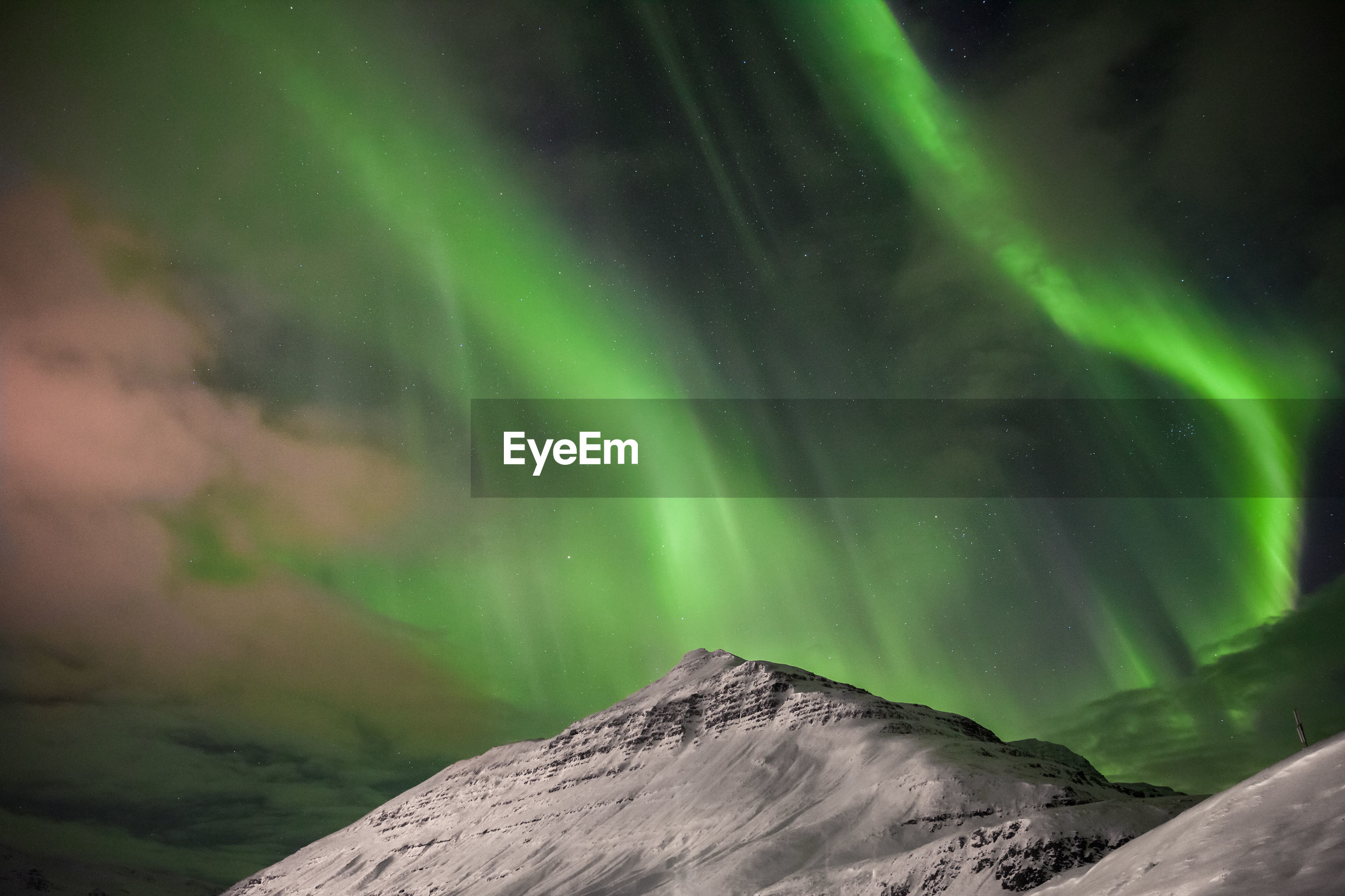 Low angle view of aurora borealis over snowcapped mountain at night