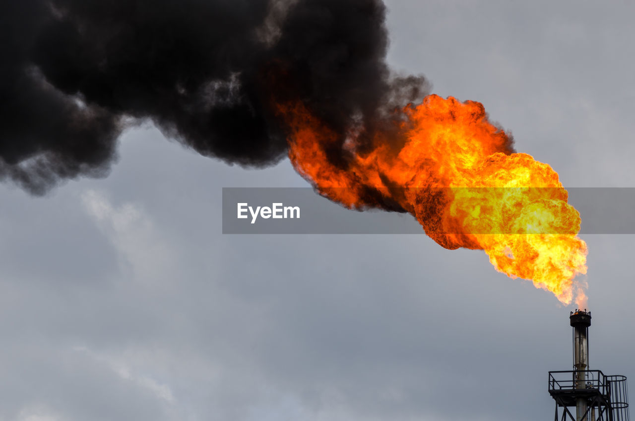 Oil Refinery Flare Stack Against Sky