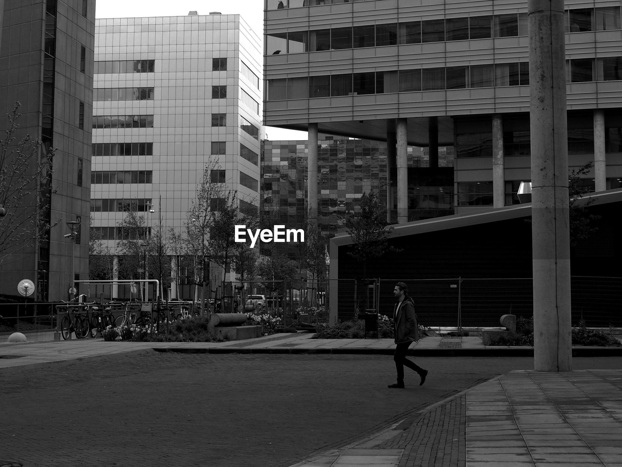MAN WALKING ON MODERN OFFICE BUILDINGS