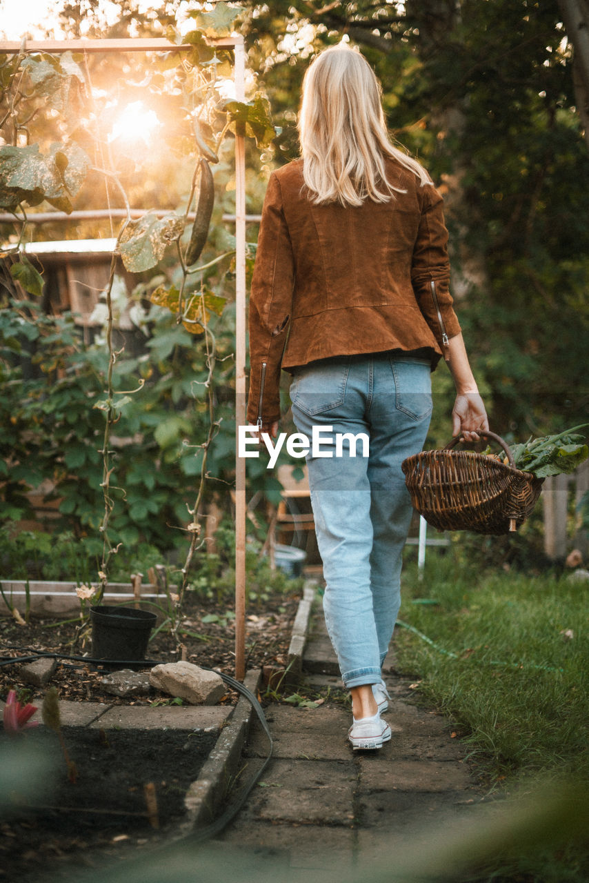 FULL LENGTH OF WOMAN STANDING IN BASKET OF PLANTS
