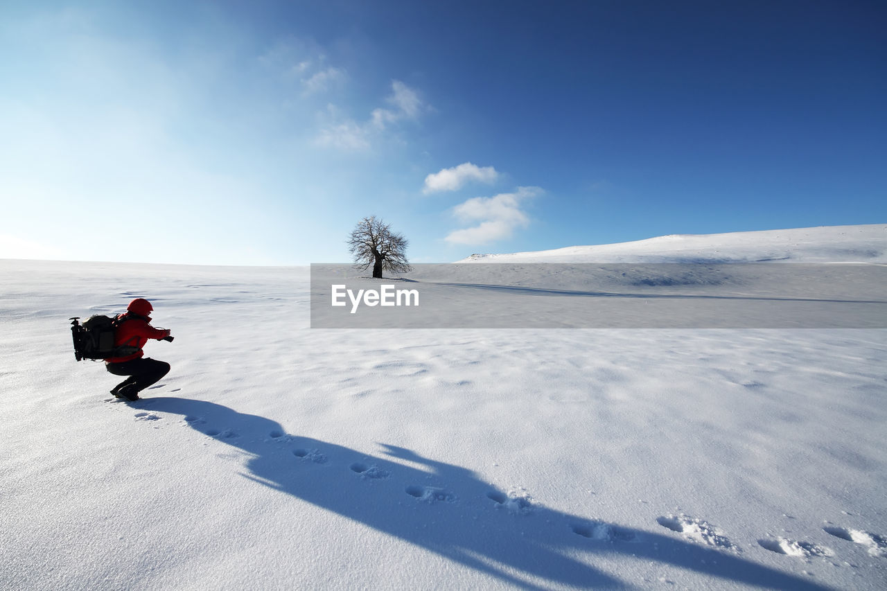 Scenic view of snowy field against sky