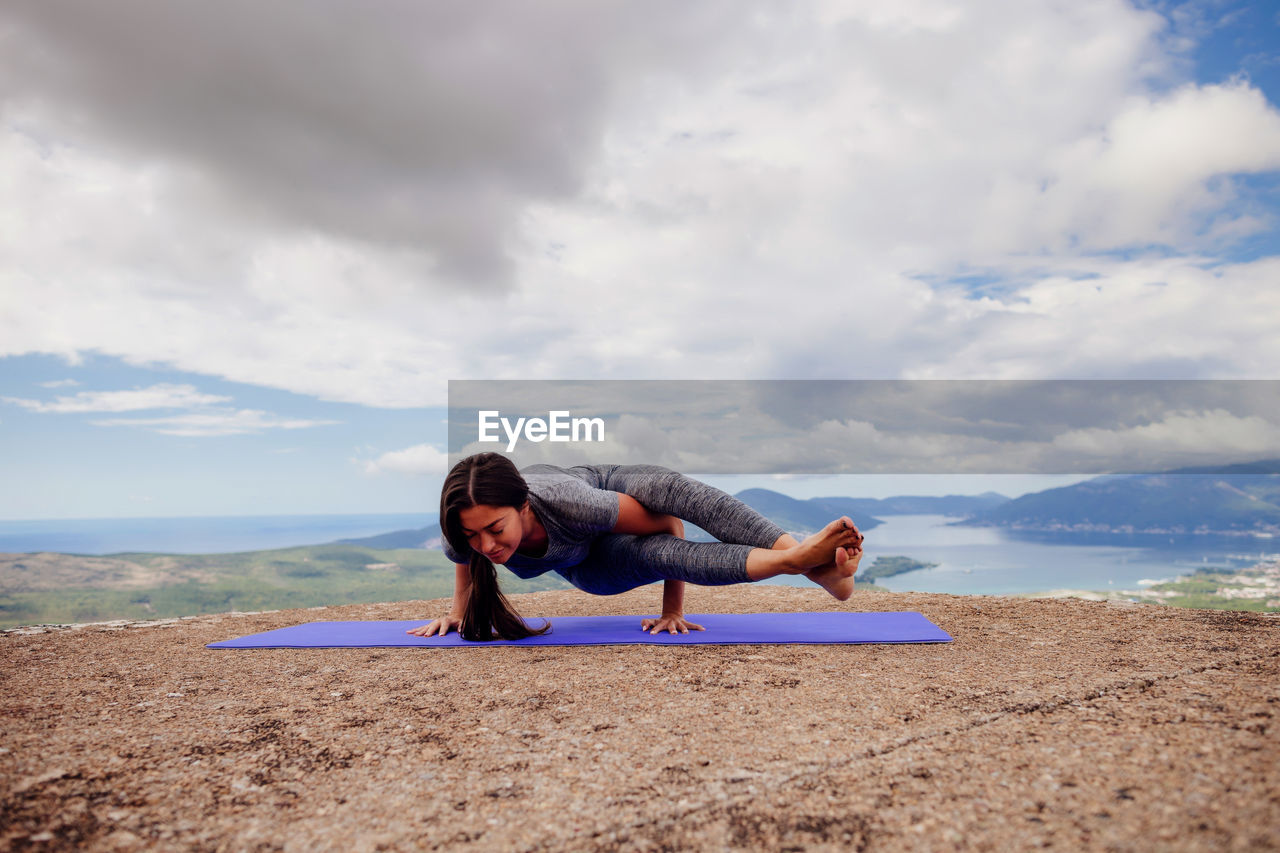 Woman Exercising On Mountain Against Cloudy Sky