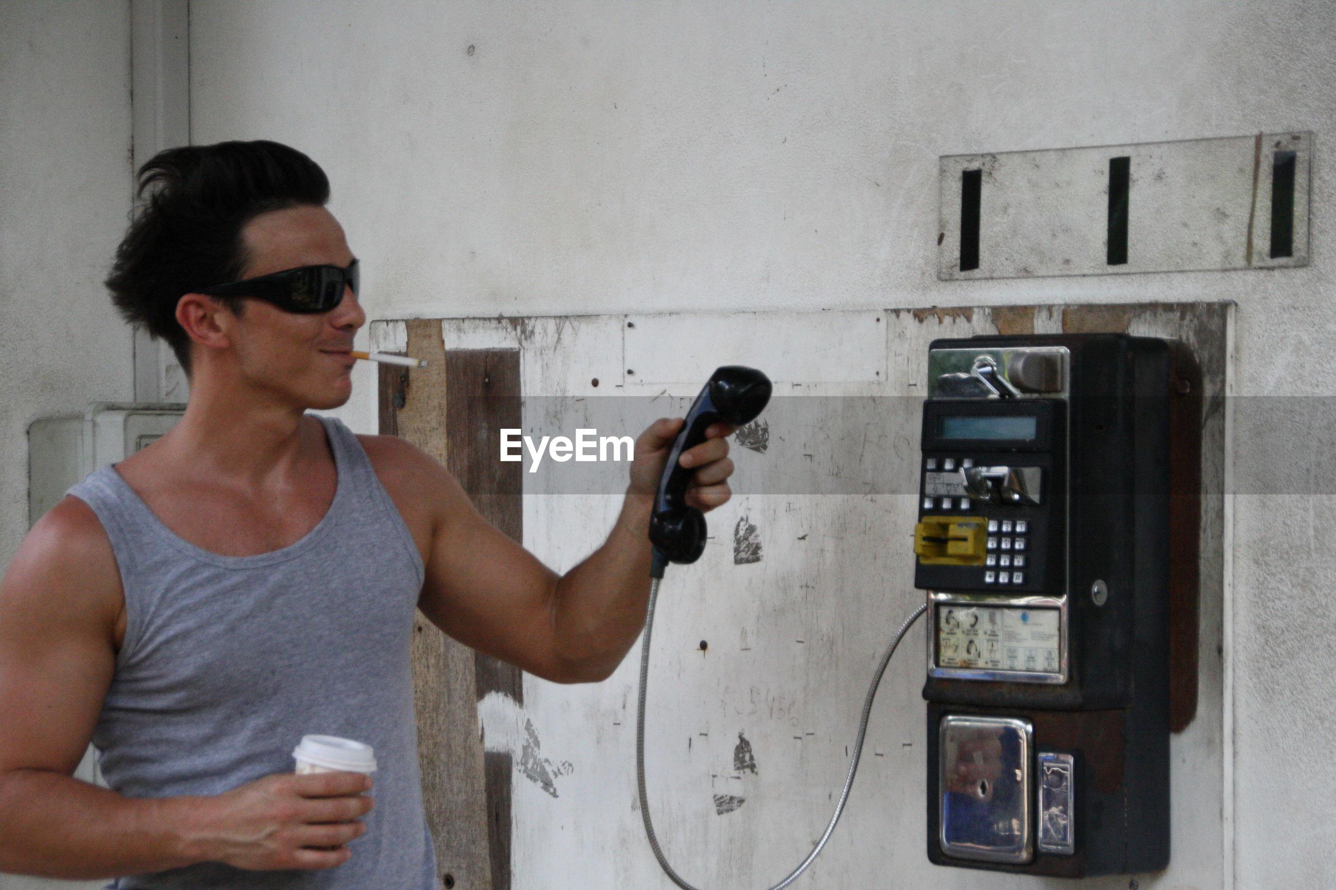 Man using payphone