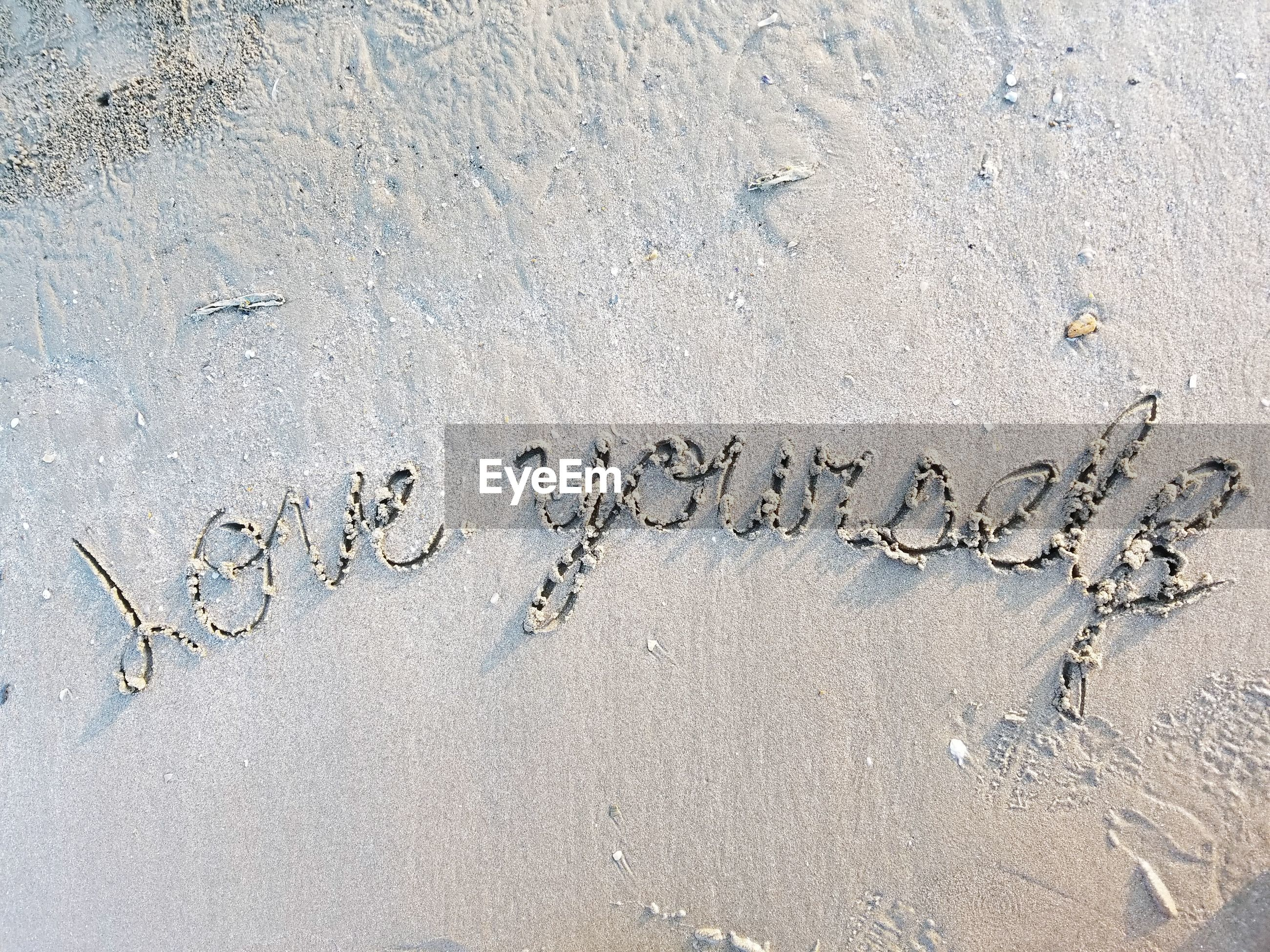 HIGH ANGLE VIEW OF TEXT WRITTEN ON SAND