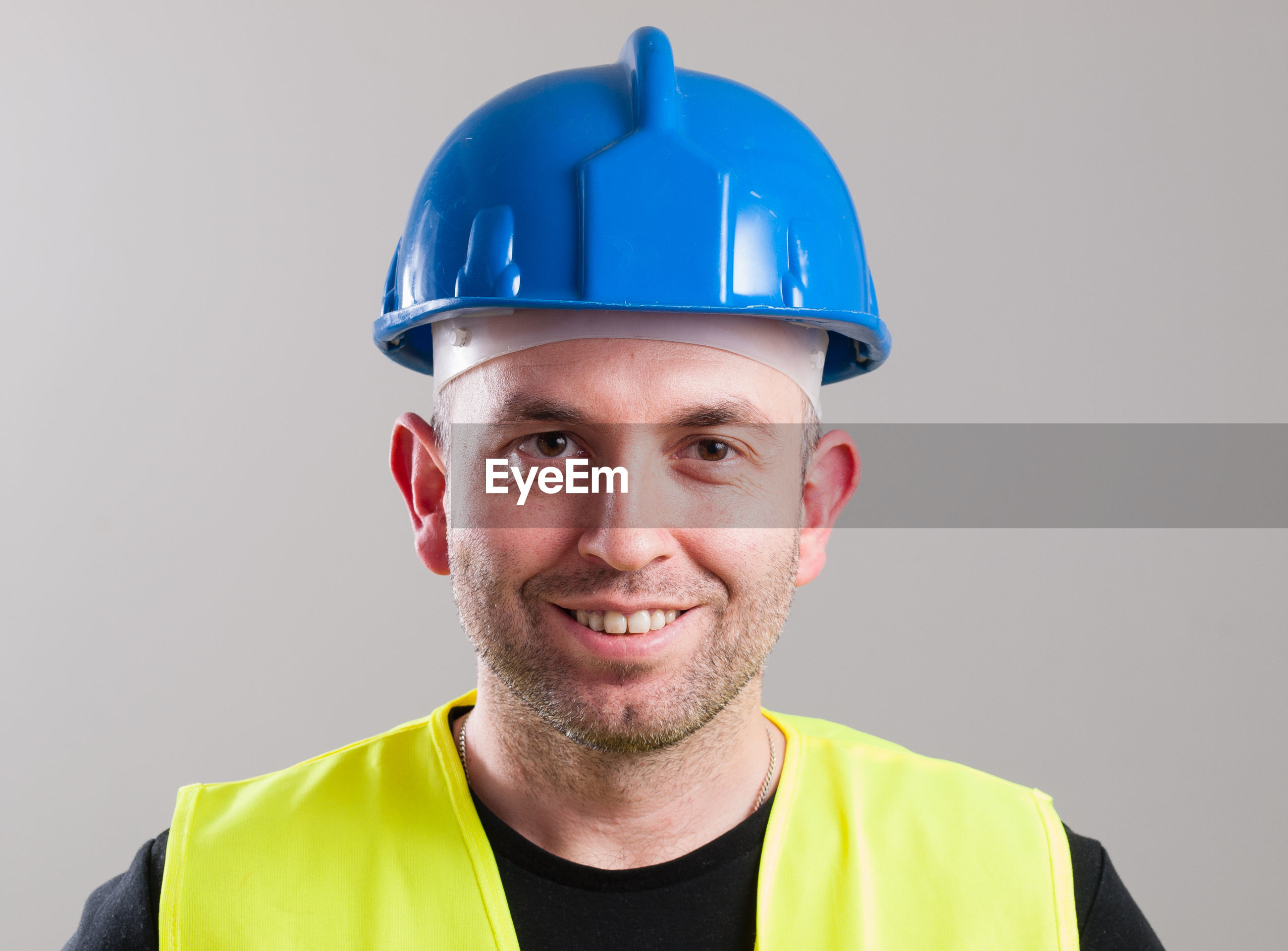 Portrait of smiling construction worker against gray background