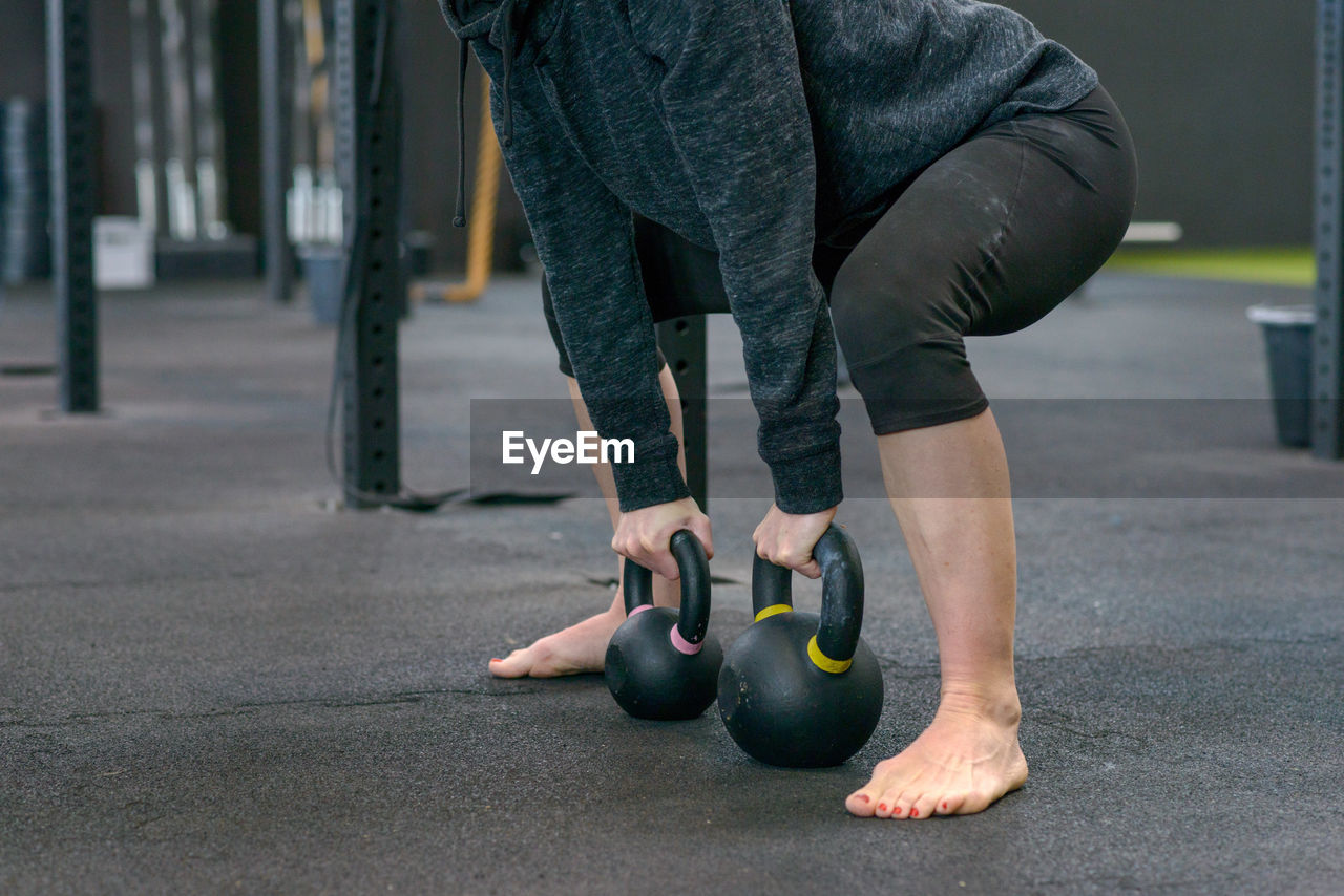 Low Section Of Female Athlete Exercising With Kettlebells In Gym