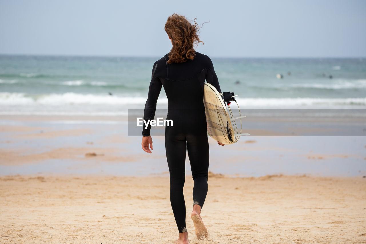 REAR VIEW OF WOMAN WALKING ON BEACH AGAINST SEA