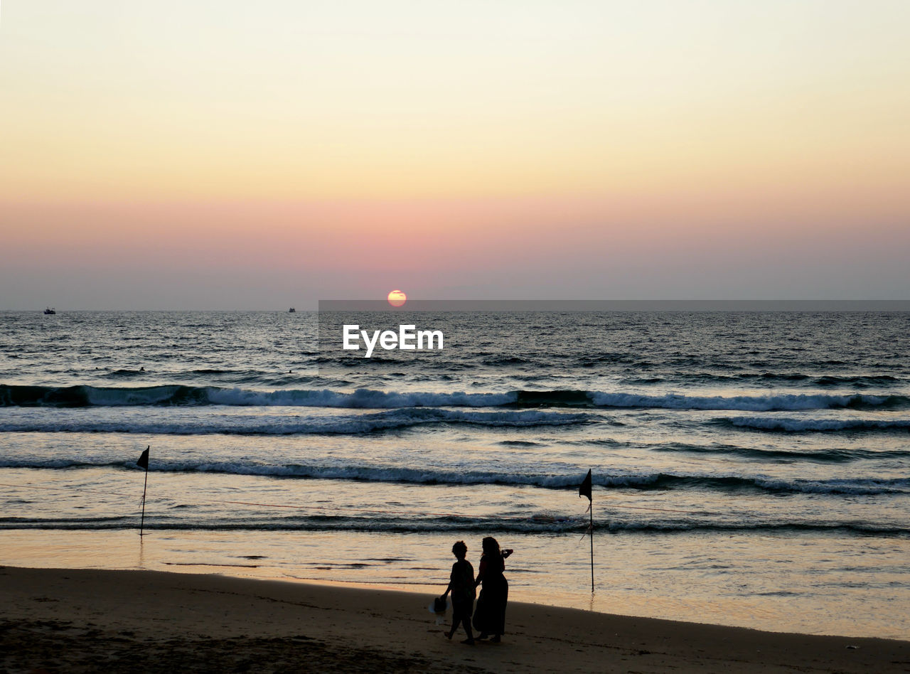 sea, sky, sunset, beach, land, water, horizon over water, real people, horizon, beauty in nature, scenics - nature, two people, orange color, nature, people, men, leisure activity, togetherness, lifestyles, sun, outdoors, couple - relationship