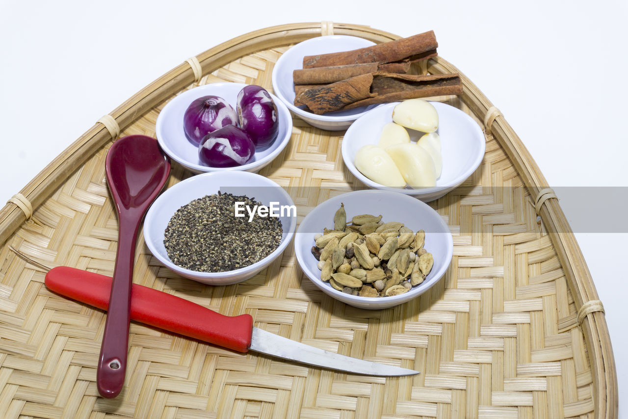 High angle view of spices and vegetables on wicker basket on white background