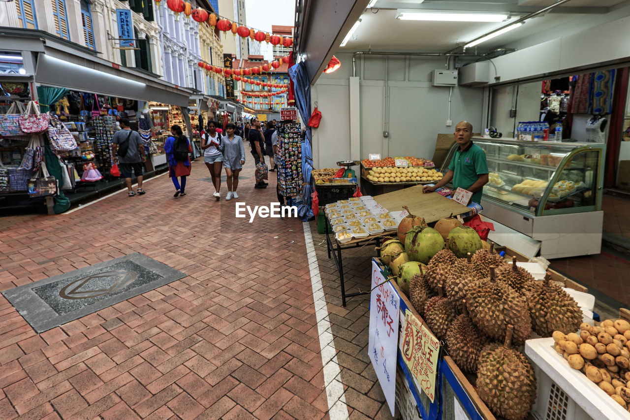 food, food and drink, market, retail, healthy eating, market stall, real people, for sale, group of people, men, freshness, fruit, large group of people, small business, crowd, women, choice, adult, shopping, buying, retail display, sale, street market