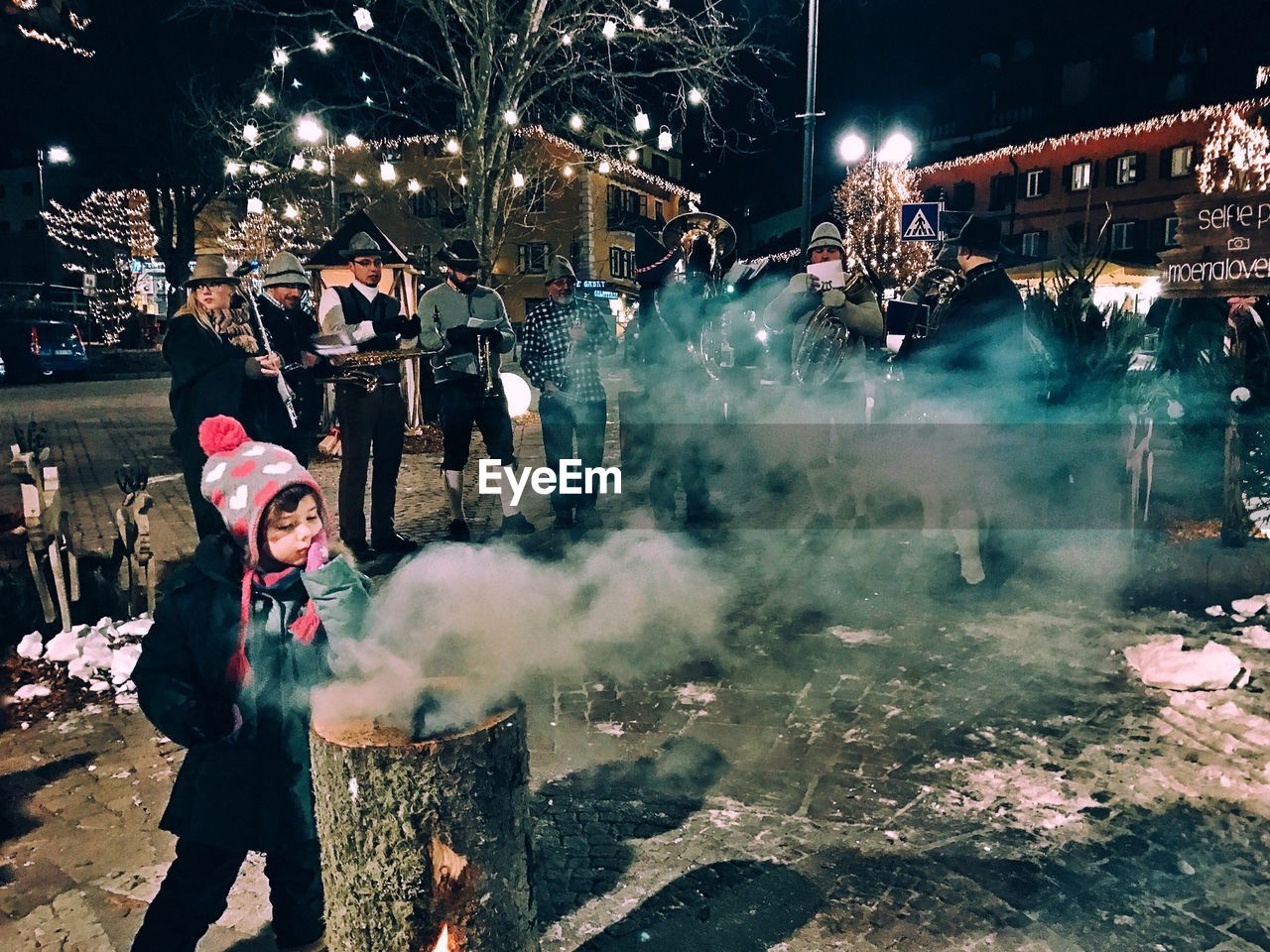 smoke - physical structure, night, real people, leisure activity, risk, lifestyles, winter, celebration, outdoors, firework - man made object, enjoyment, firework display, sparkler, bad habit, snow, cold temperature, building exterior, city, warm clothing, one person, architecture, men, young adult, riot, people