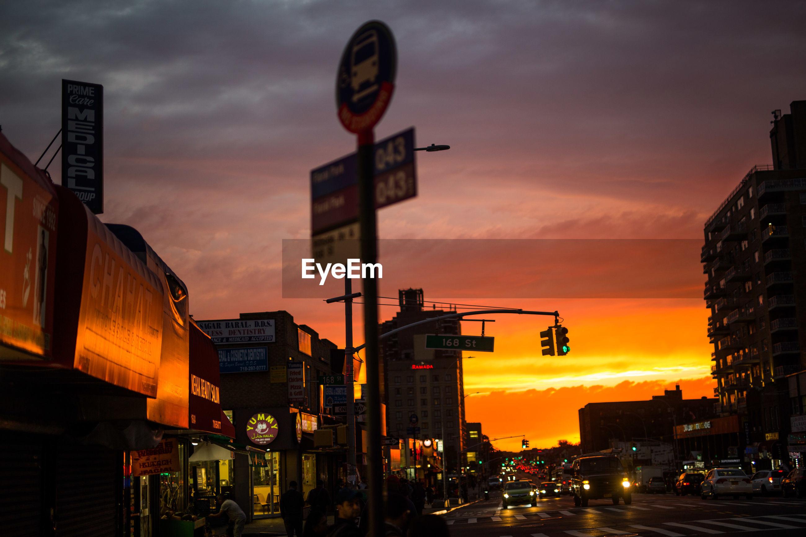 VIEW OF CITY STREET AGAINST ORANGE SKY