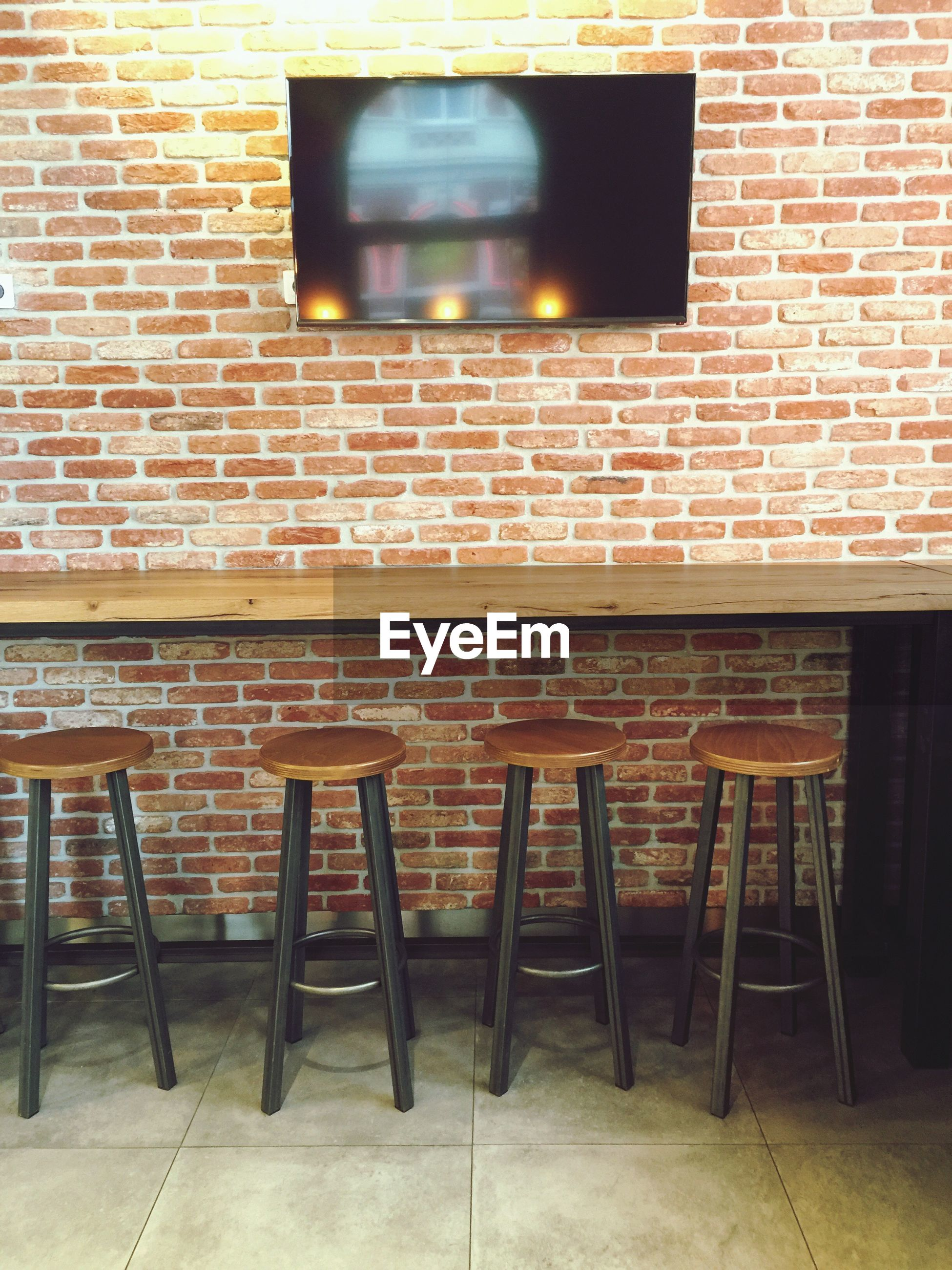 Wooden seats by table against brick wall in cafe