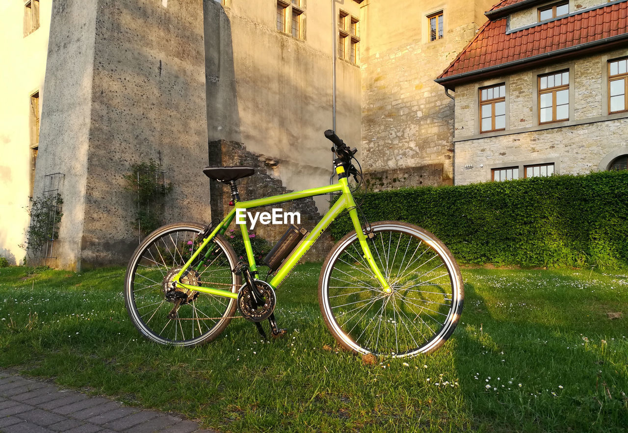 building exterior, architecture, built structure, transportation, bicycle, building, land vehicle, day, plant, mode of transportation, nature, grass, residential district, stationary, green color, outdoors, no people, house, wall - building feature, city, wheel